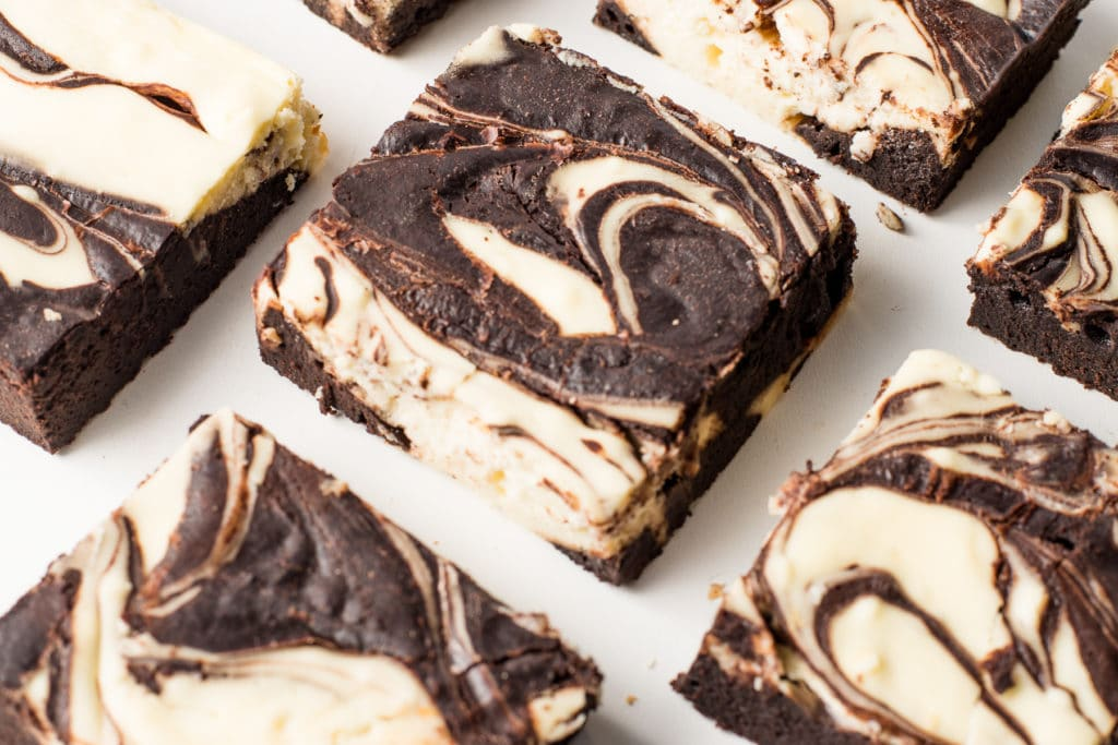 Swirled cheesecake brownies on a bright white background.