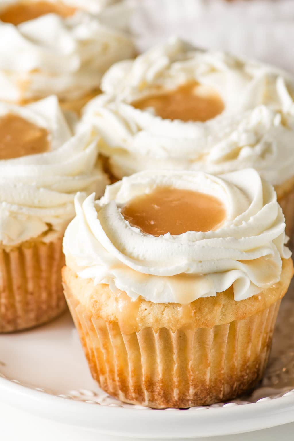 A plate of salted caramel cupcakes with piped cream cheese frosting