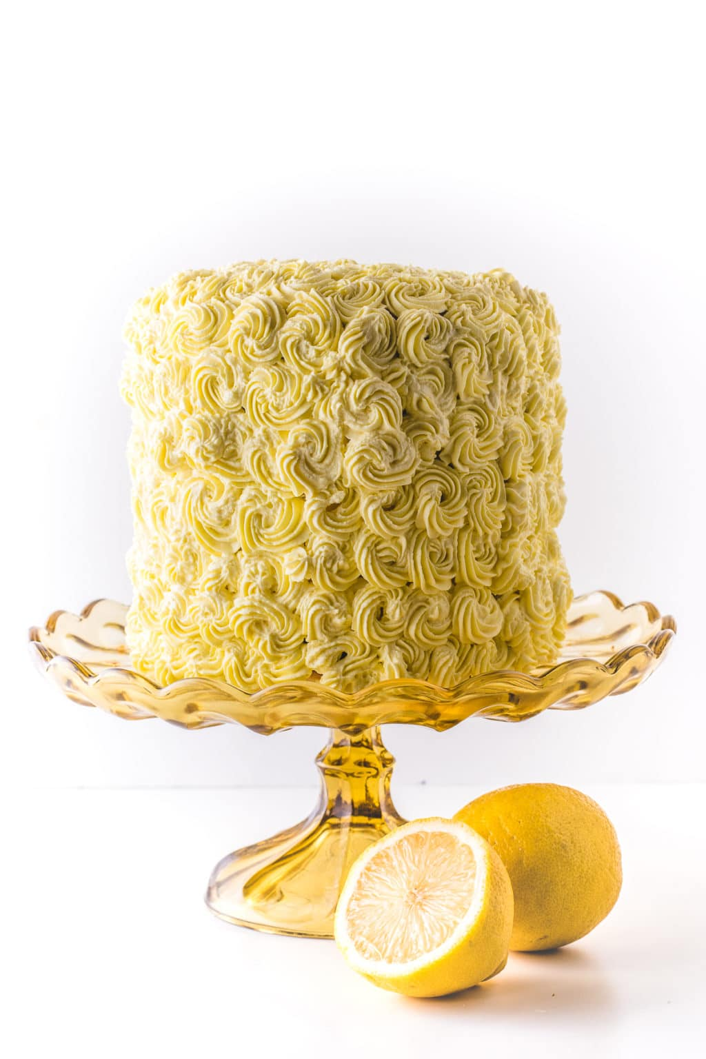 A pretty yellow cake stacked high with yellow rosettes on a yellow glass cake stand against a bright while background.