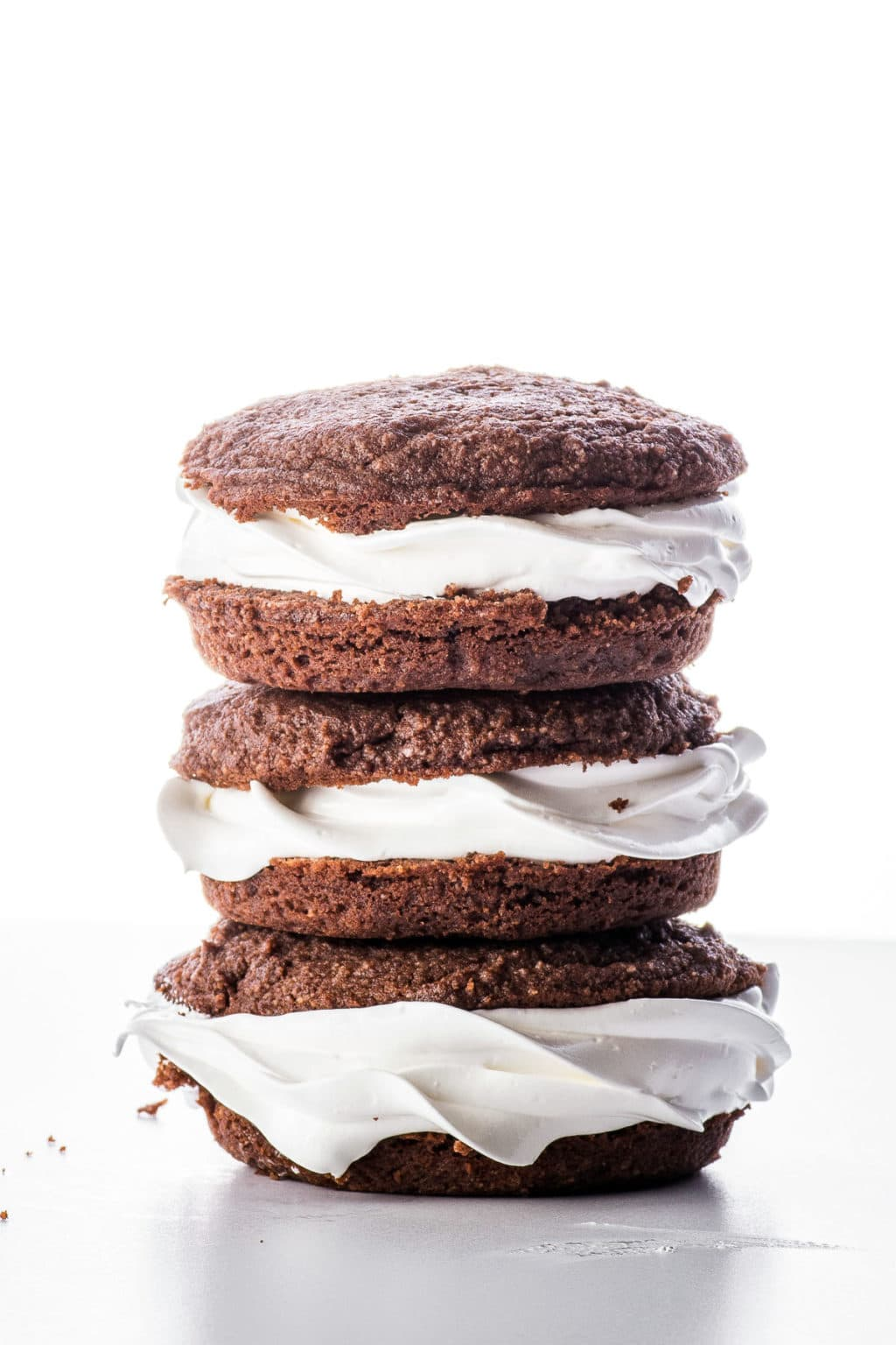Stacked chocolate keto whoopie pies on a bright white back ground