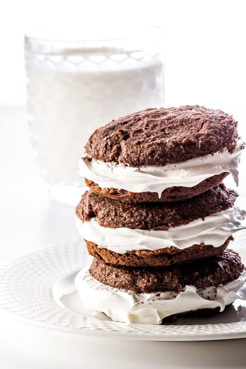 Stacked whoopie pies on a white plate in front of a glass of cashew milk