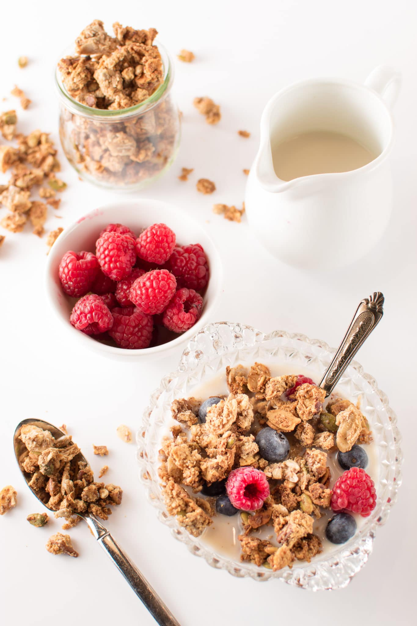 A bright white breakfast table with a bowls of low carb granola, fresh raspberries and almond milk.