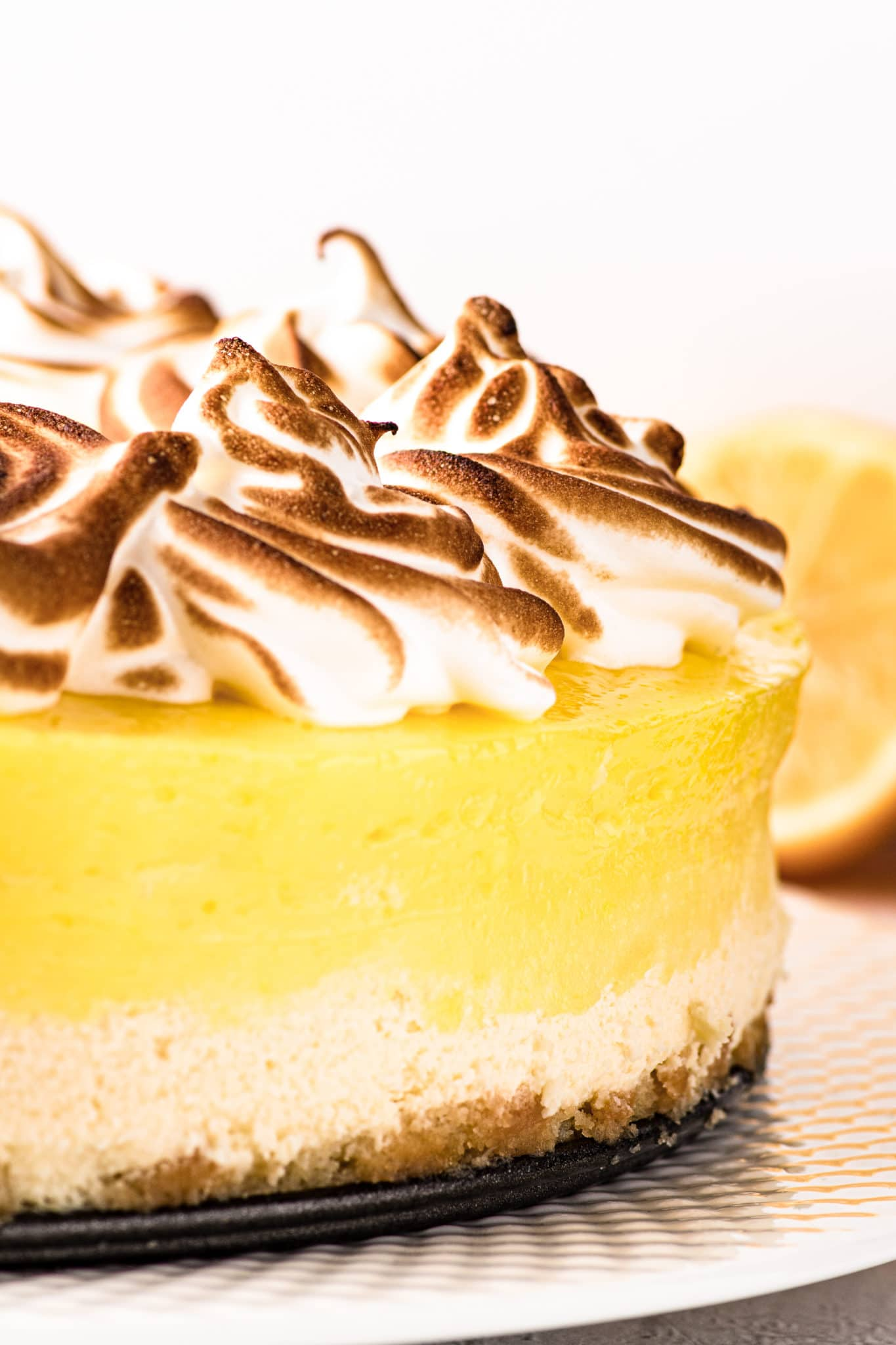 Close up photograph of a bright lemon curd topped cheesecake with toasted swirled meringue.