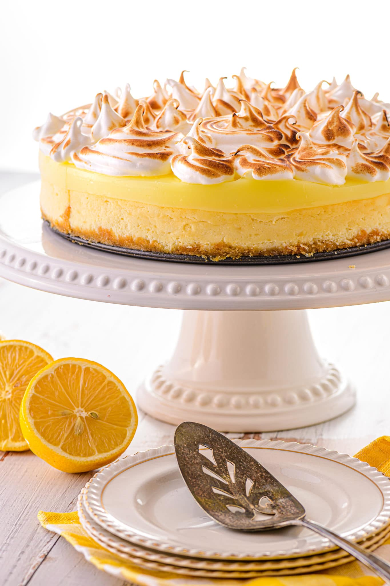 Lemon Cheesecake topped with toasted meringue on a white cake stand.