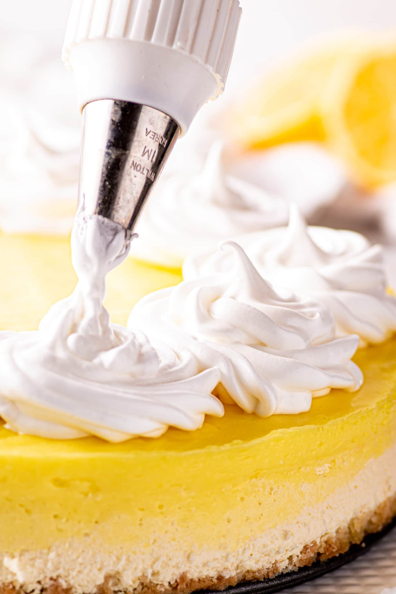 Meringue being pipped into piles of swirls on top of a bright lemon cheesecake.