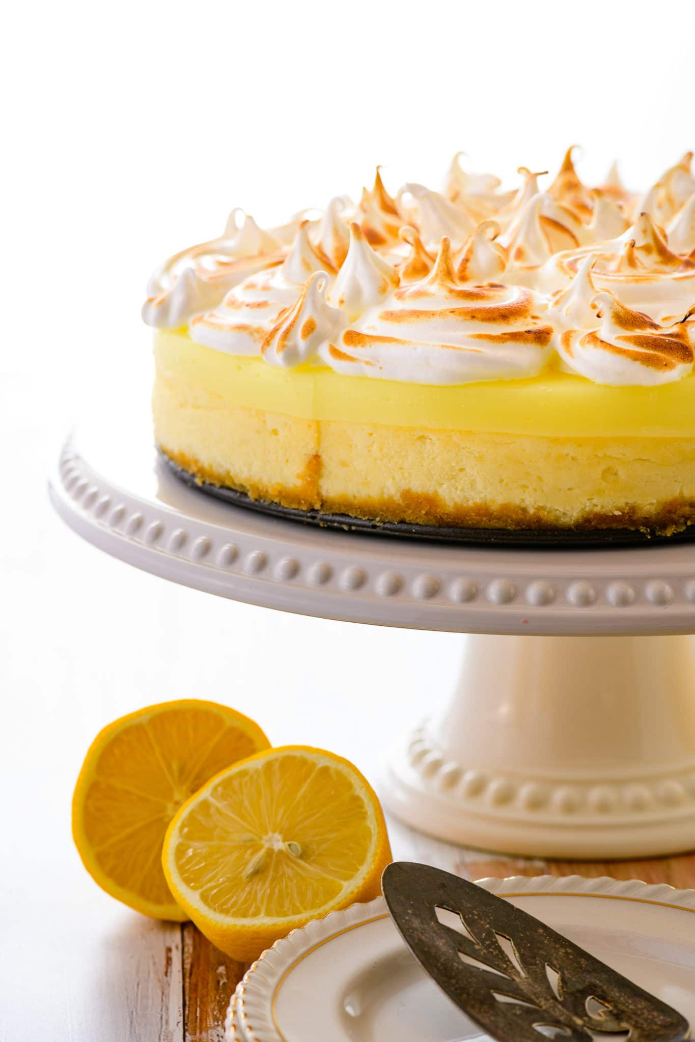 Low carb lemon curd topped cheesecake on a rustic white wooden table top.