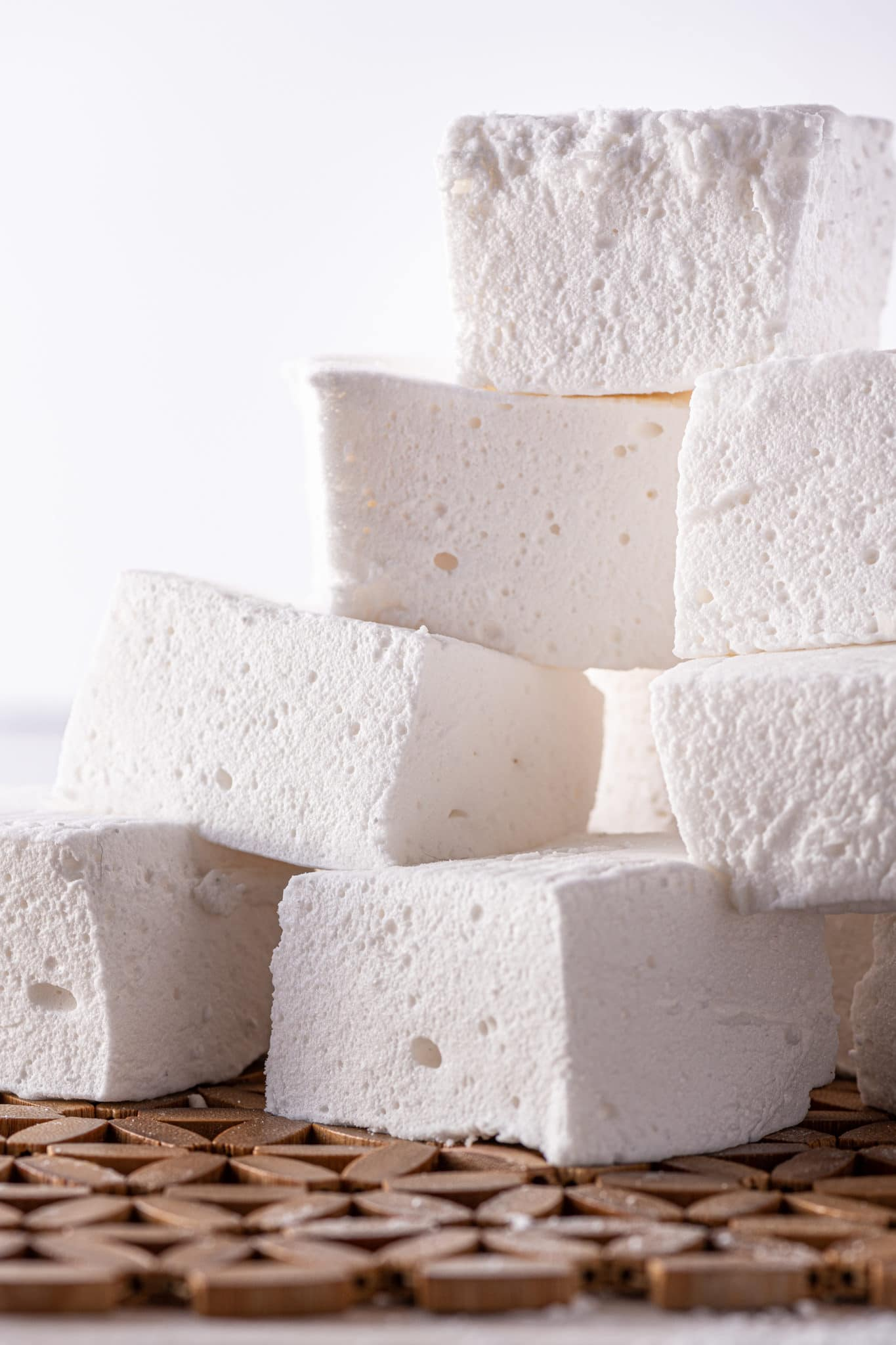 stack of fluffy square shaped marshmallows on a bright white backgrond