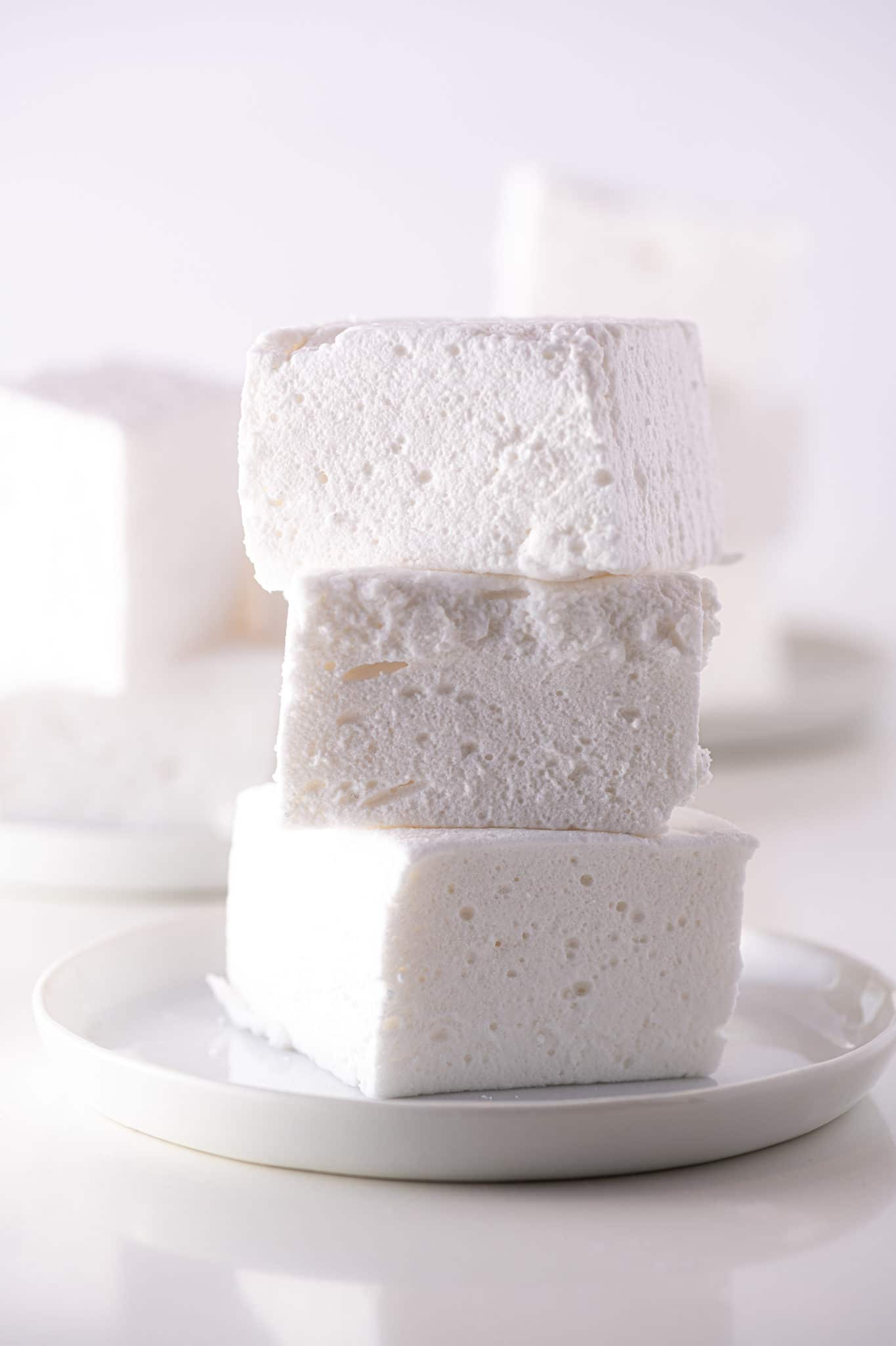 Stack of homemade vanilla sugar-free marshmallows on a white plate against a white background