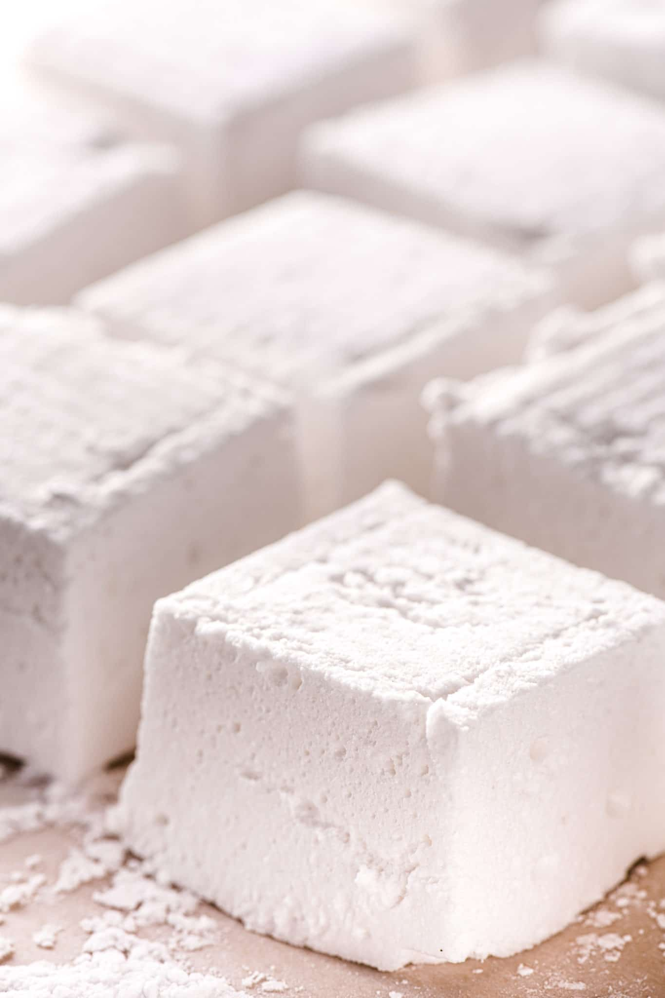Square vanilla keto marshmallows lined up on parchment paper coated in sugar-free sweetener.