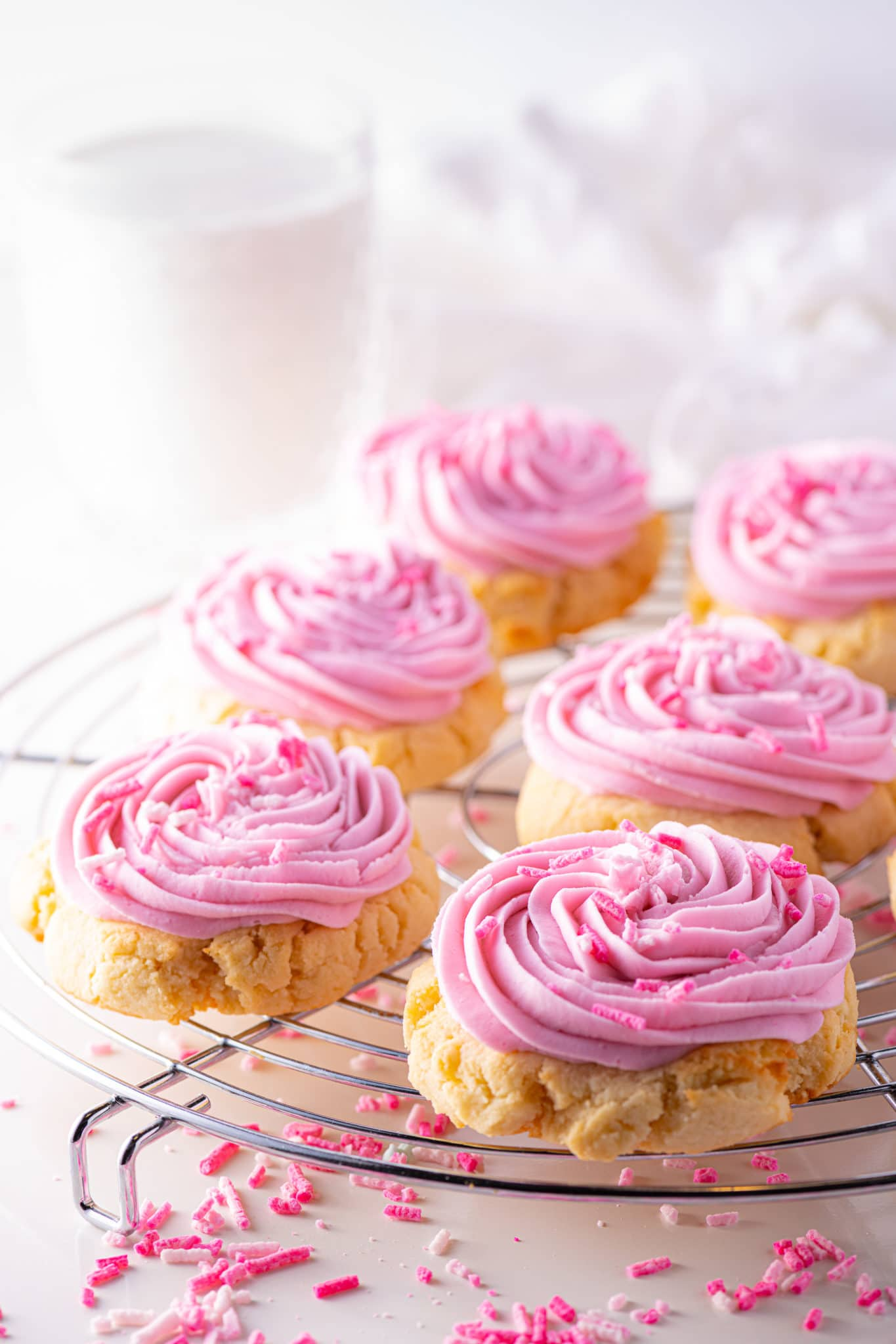 Pink sugar cookies on a cooling rack with scattered pink sprinkles and a glass of almond milk in the background