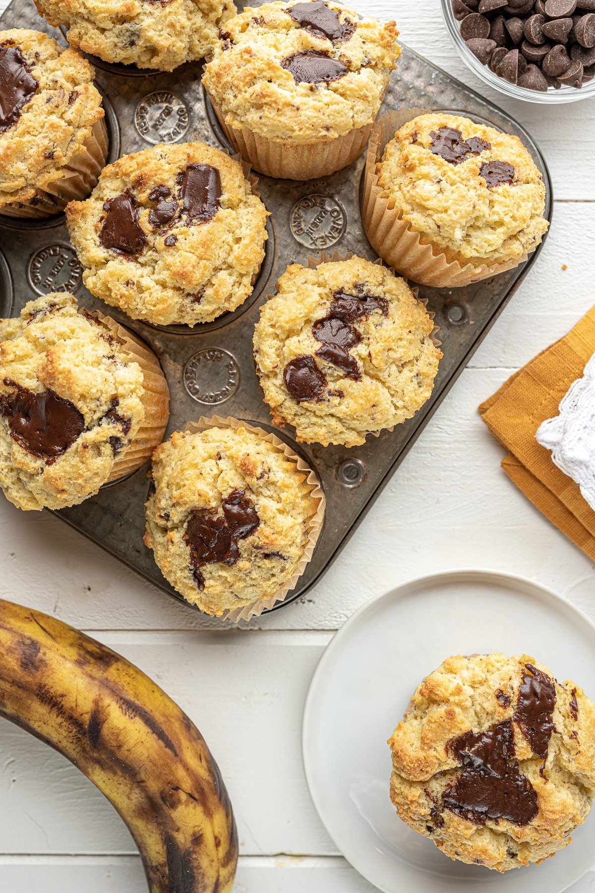 A top-down display of muffins with a ripe banana and a yellow napkin.