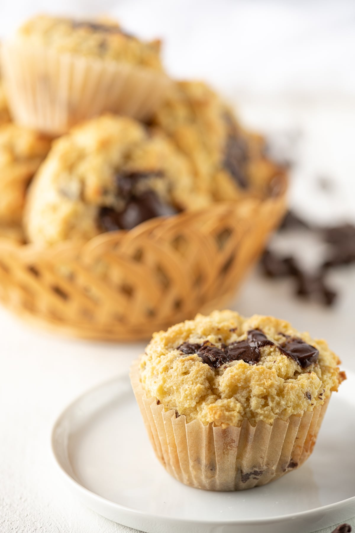 A chocolate chunk banana muffin on a white plate with a basket of muffins in the background.