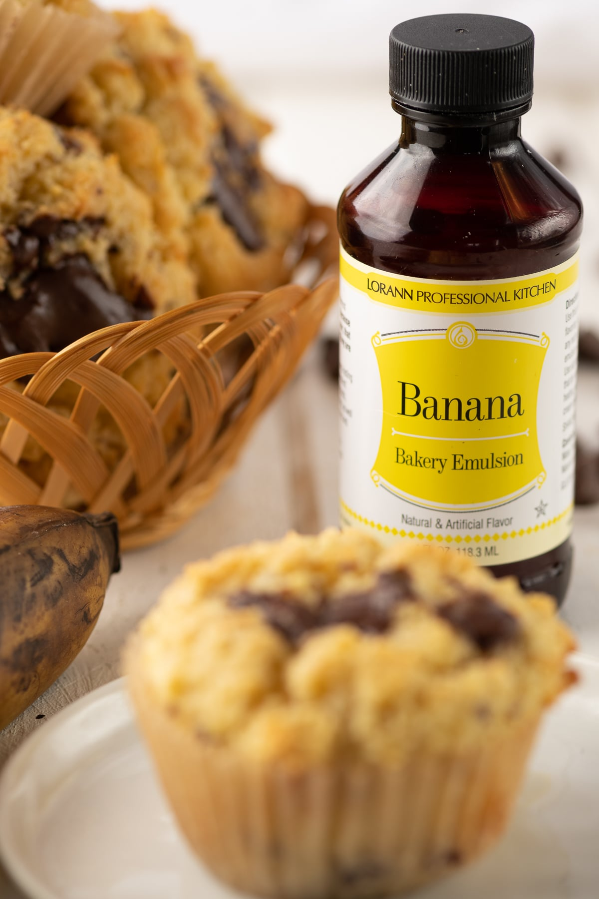 A bottle of banana bakery emulsion with a blurred muffin in the foreground.