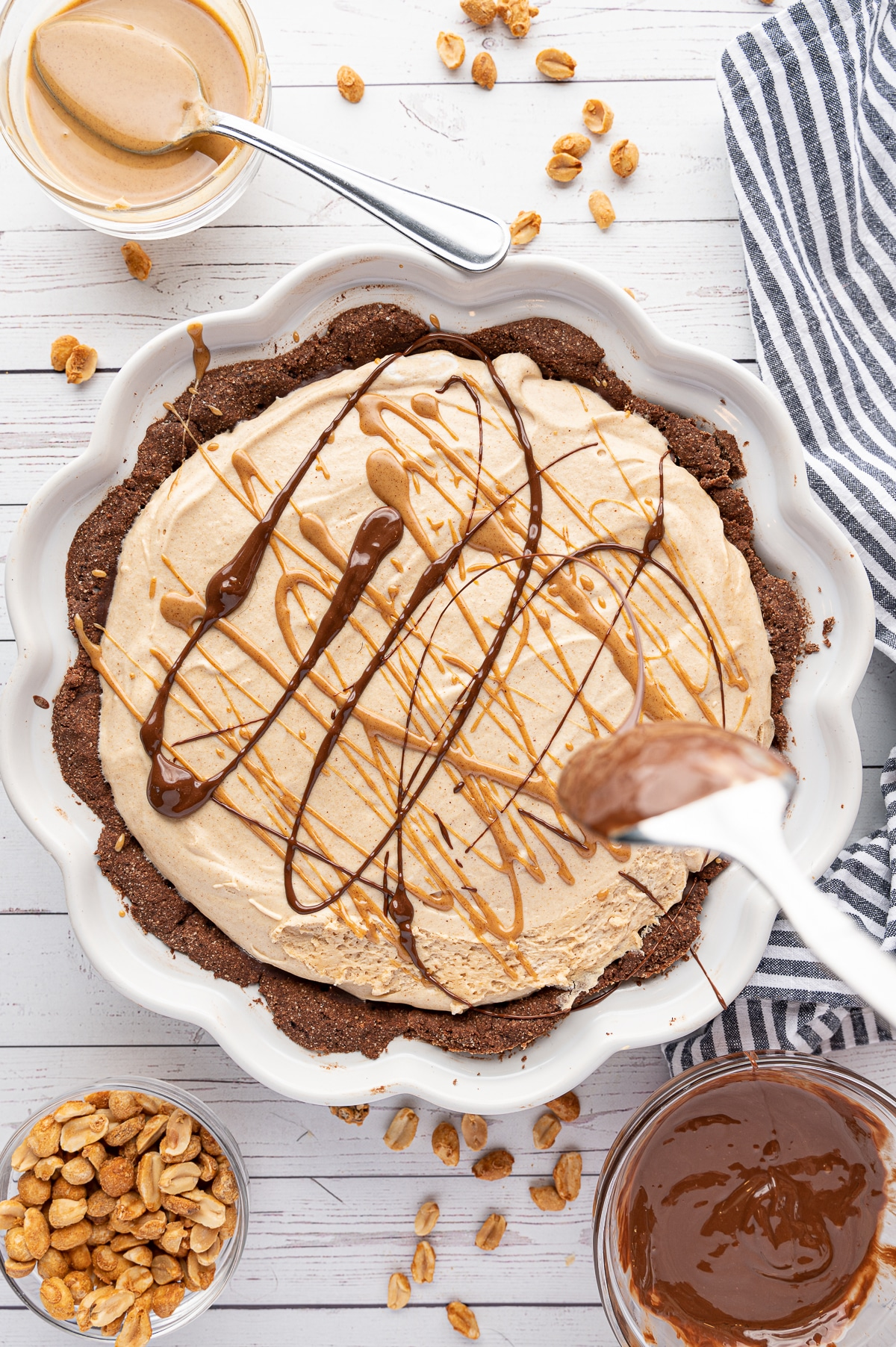 A chocolate crusted peanut butter pie on a white wooden background. Spoon in forefront swirling melted chocolate ganache over the pie.