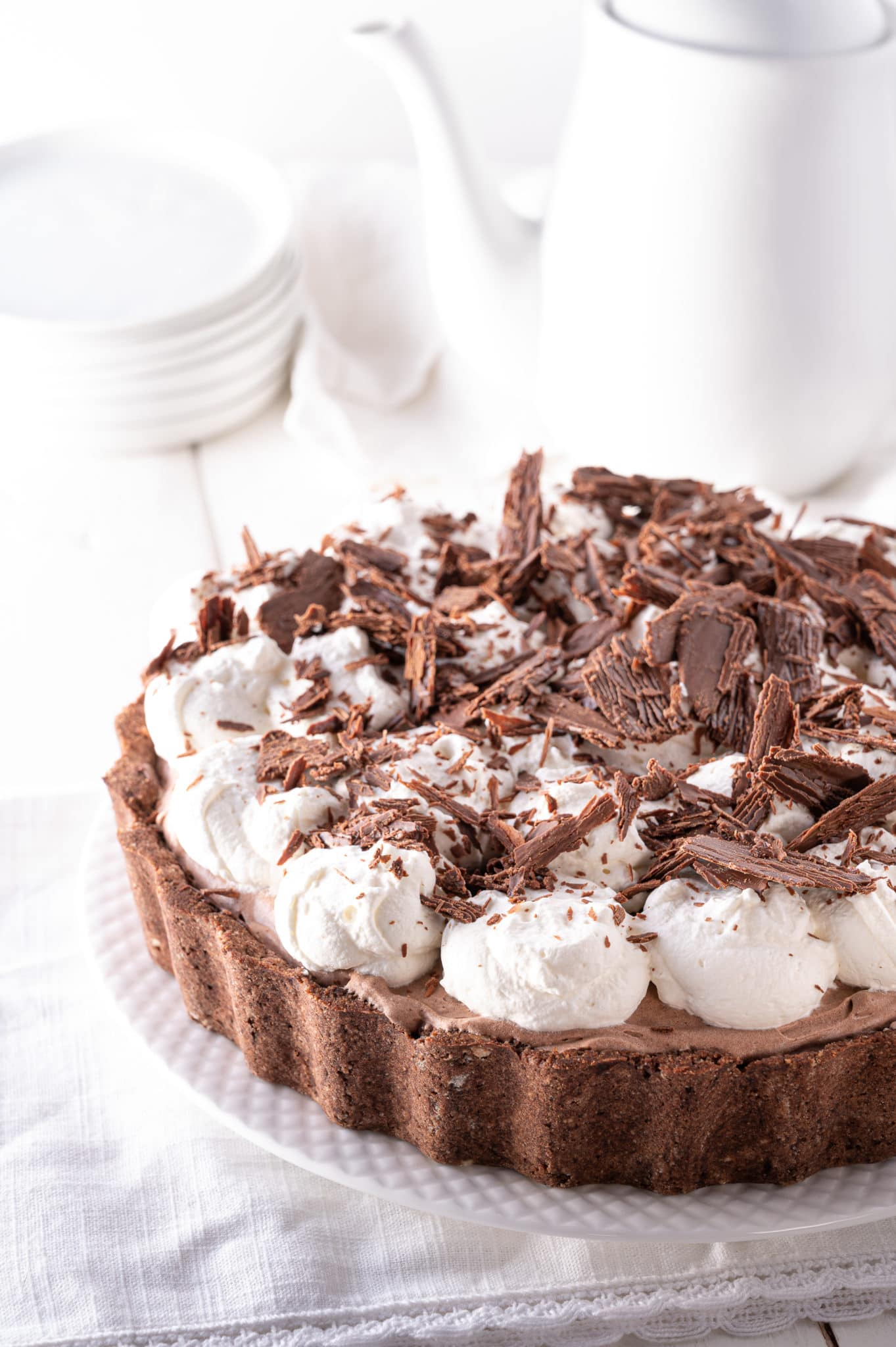 A low carb chocolate silk pie topped with whipped cream and chocolate shavings on a bright white tabletop.