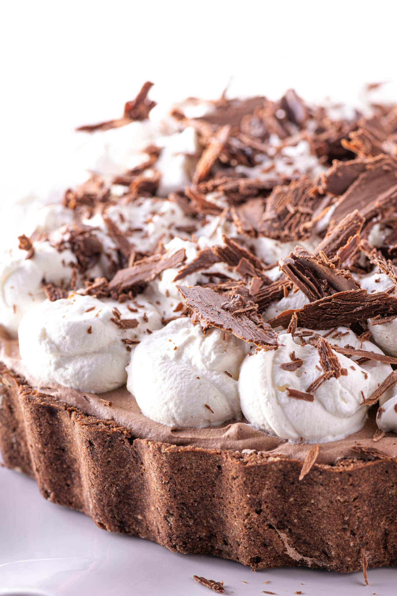 A close up image of a chocolate pie crust filled with chocolate filling and topped with whipped cream and chocolate shavings.