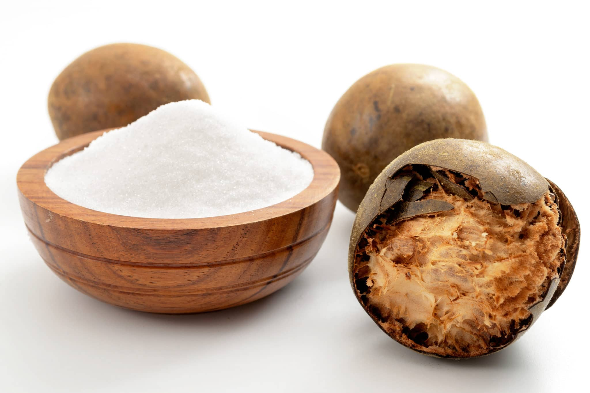 A wooden bowl filled with white granulated monk fruit sweetener, with an open monk fruit sitting beside the bowl