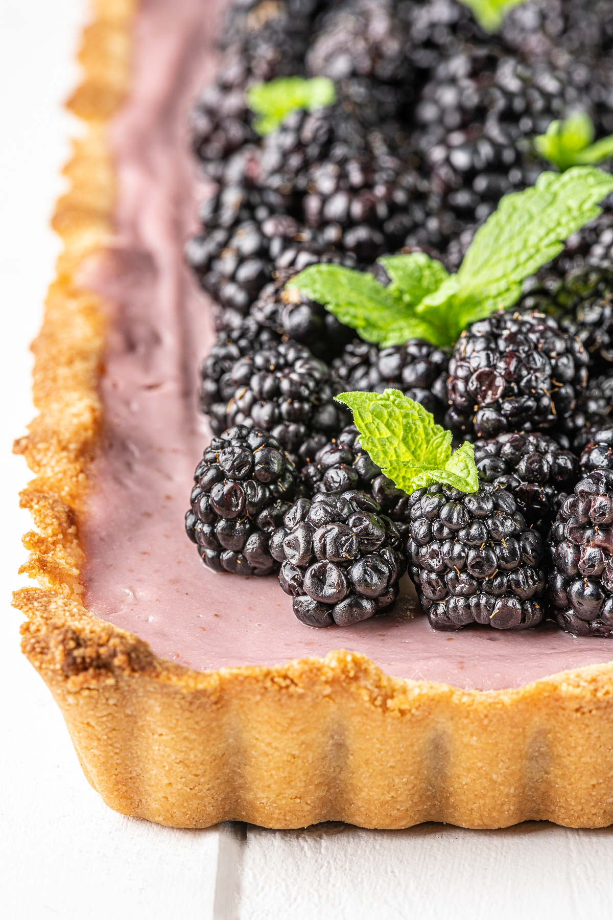 A close up image of a fresh blackberry tart with golden baked ruffle crust and fresh glistening blackberries garnished with sprigs of bright green mint leaves