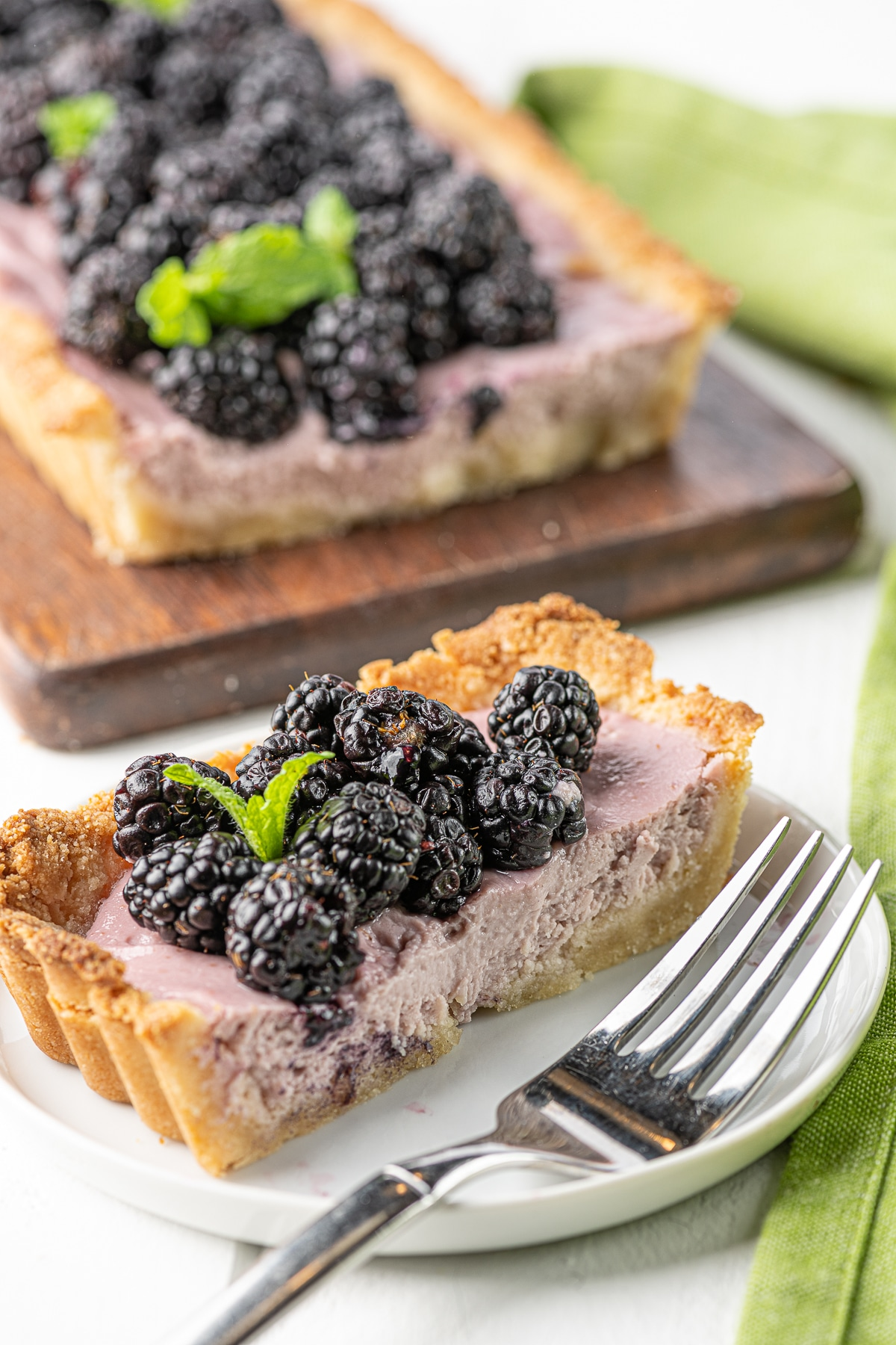 A slice of blackberry tart on a bright white plate with fork, with a green out of focus napkin  and tart in the background
