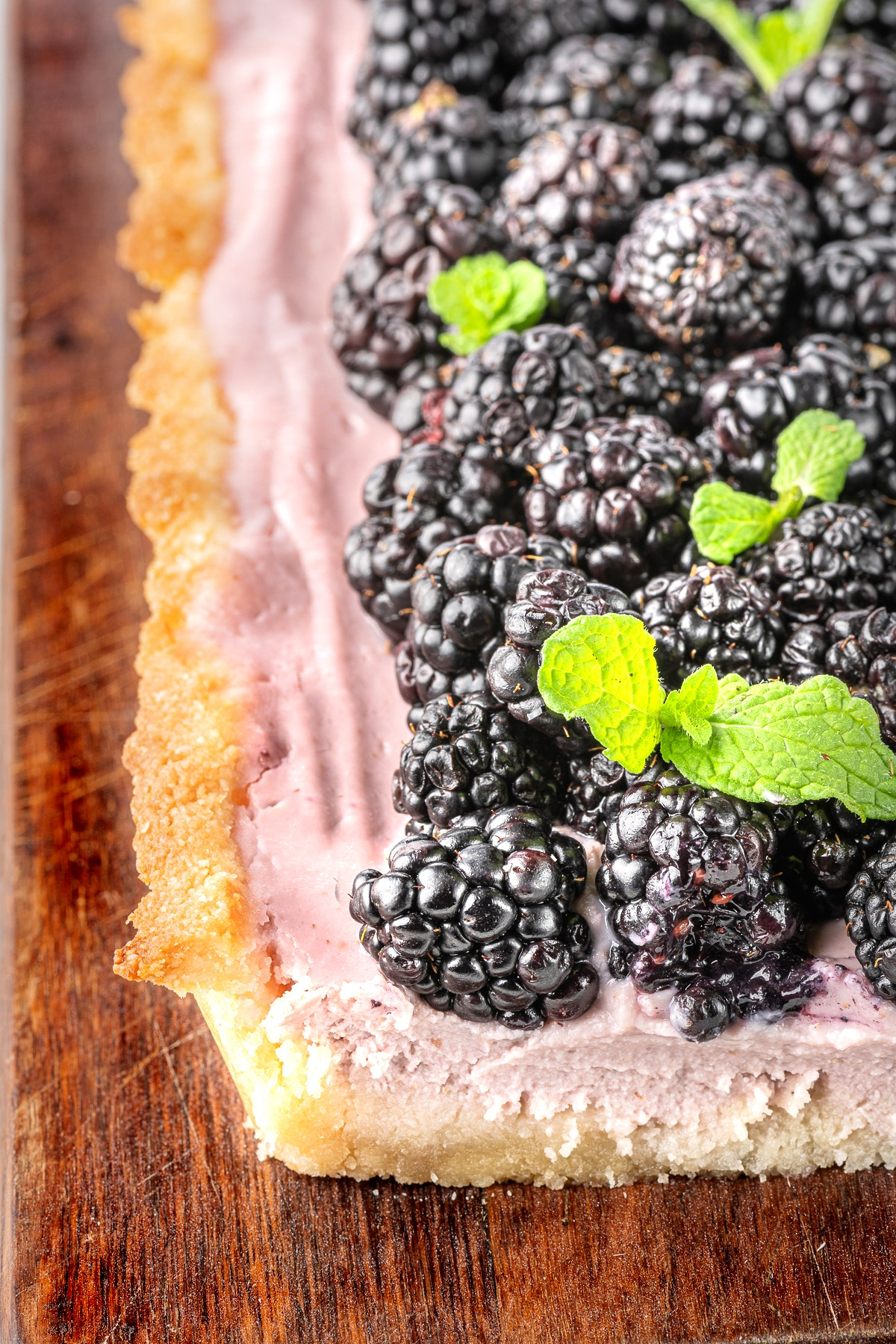 blackberry tart dessert on a rustic wooden cutting board with the edge of the tart sliced to show the inside creamy filling