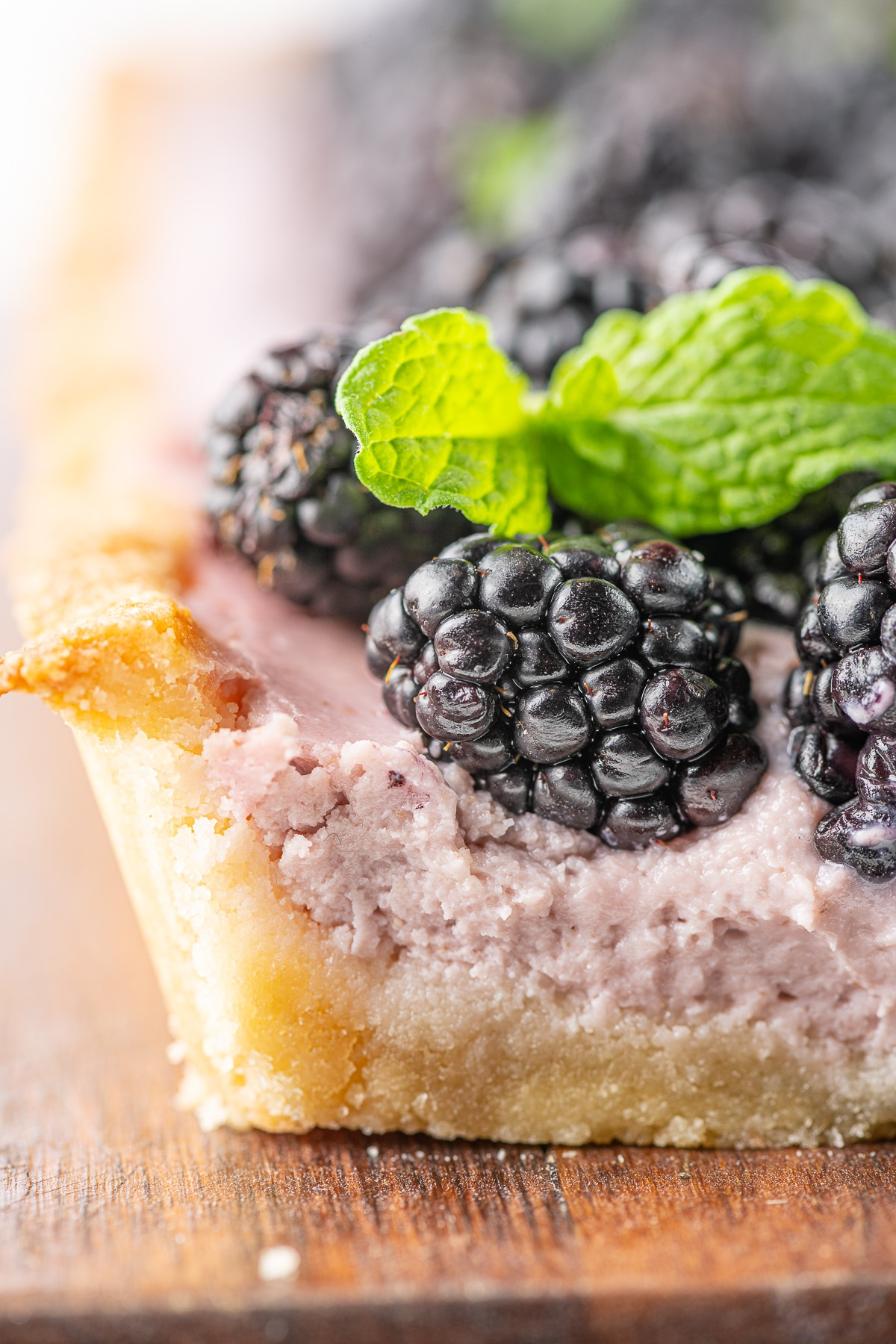 Extreme close of the edge of a slice of blackberry tart on a rustic wooden cutting board