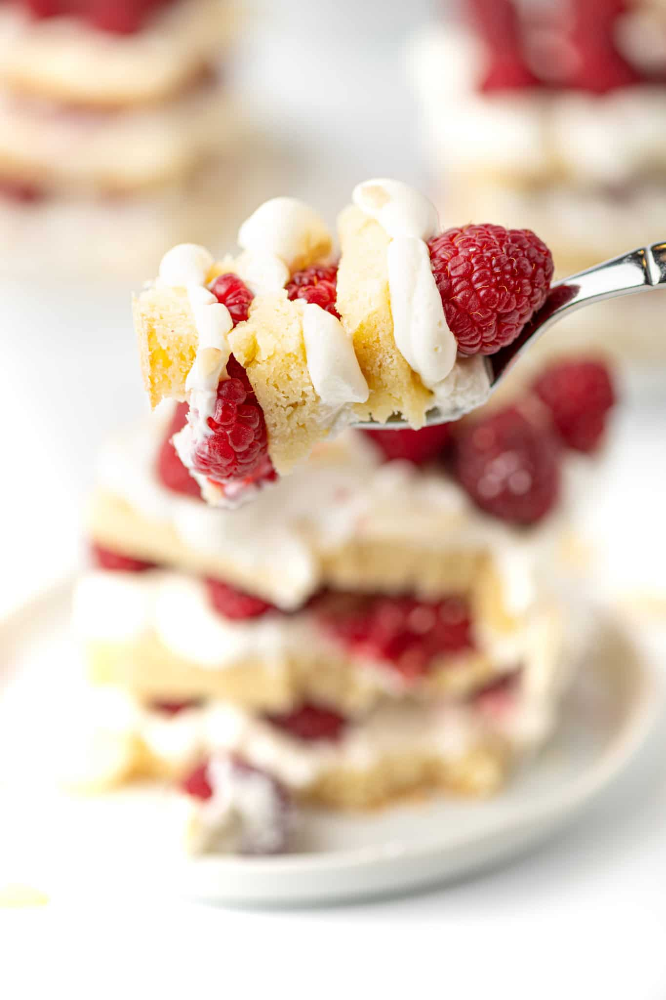 A close up shot of a piece of low carb short cake with layers of cake, whipped cream filling, and raspberries on a small dessert fork.  Blurred background.