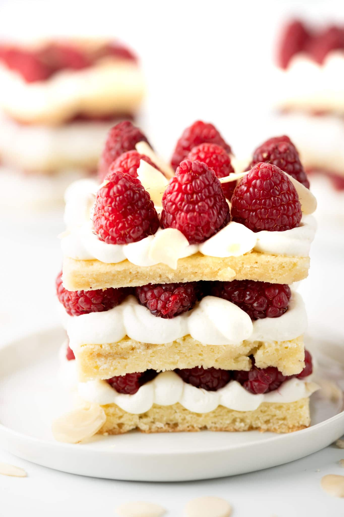 Up close shot of a raspberry shortcake with oozing layers of fresh almond cream and bright fresh red berries all on a bright white background.