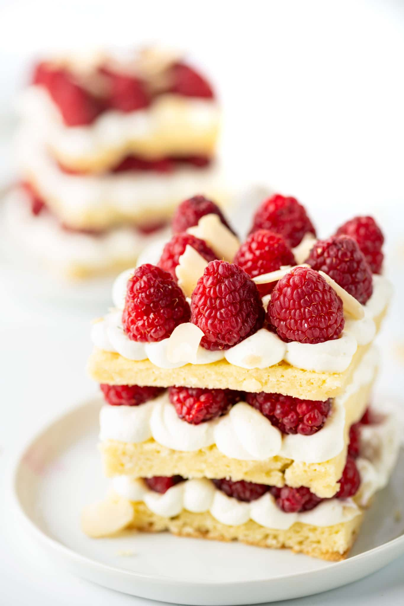 Layered low carb shortcake desserts with raspberries and whipped cream against a bright white background.