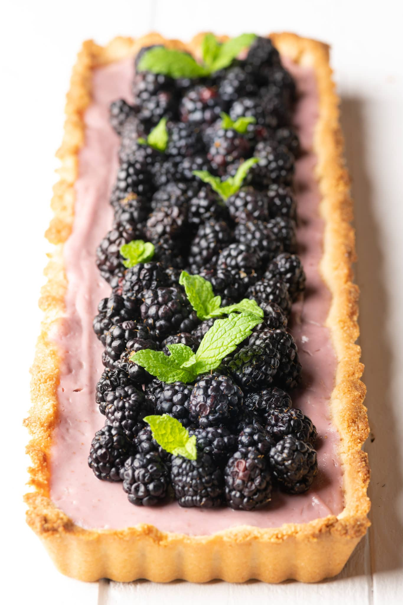 Rectangular shaped tart with golden crust and light purple filling topped with fresh blackberries and sprigs of mint.