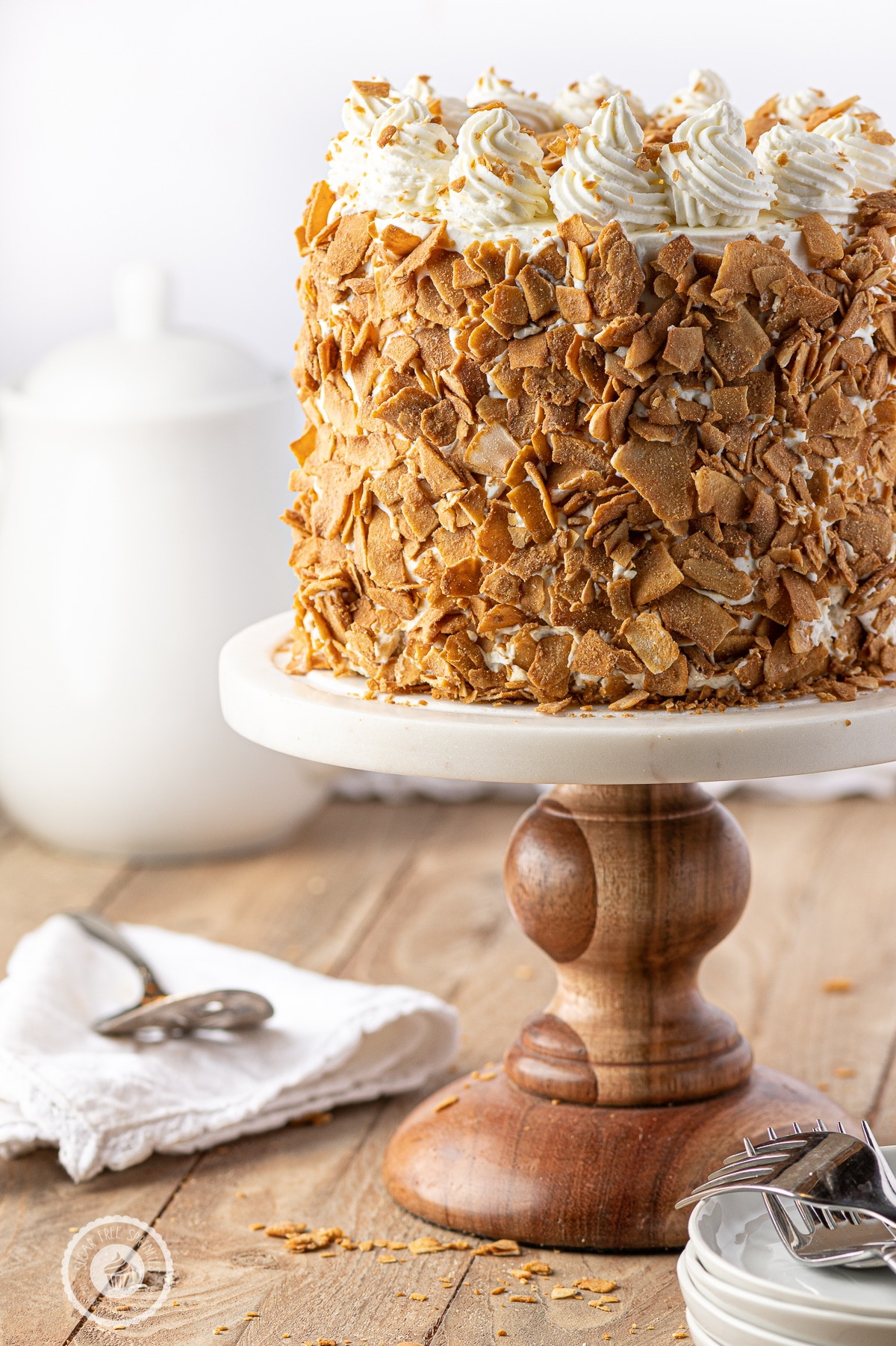 A low carb coconut cake with toasted bits of large flake coconut layered around the outside.  The cake is on a wooden and marble cake stand and a rustic wooden table.