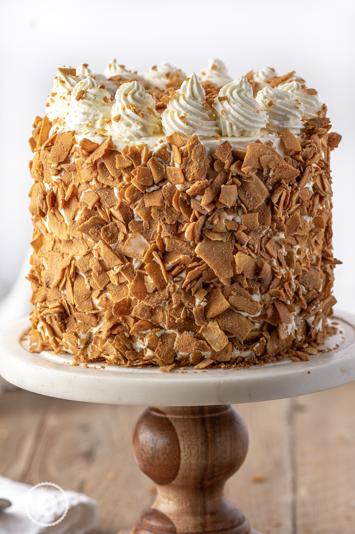 A close up photograph of a cake coated in golden brown toasted coconut on a a wood and marble cakestand