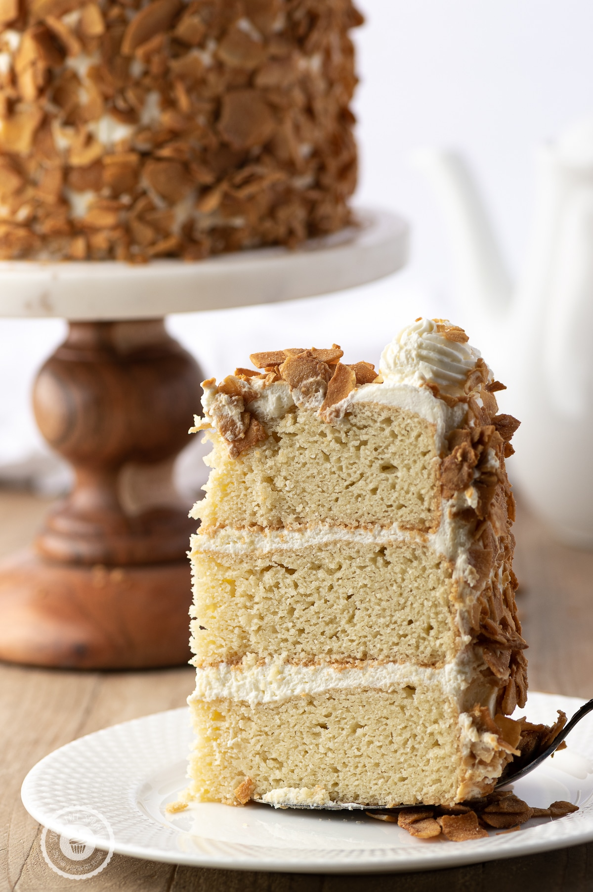 A slice of three layer coconut cake on a white plate with a rustic wooden tabletop.