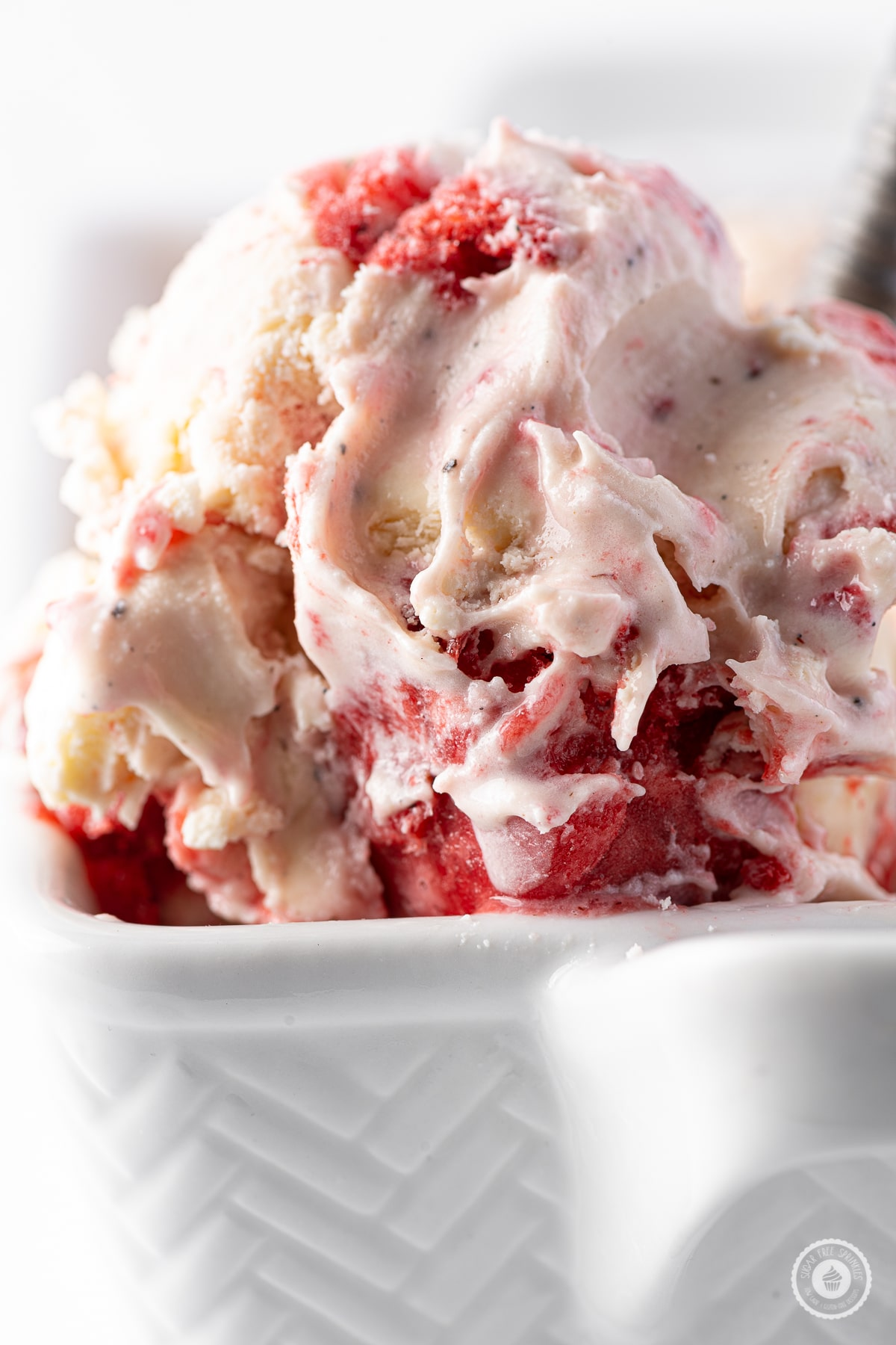 A close up photograph of a scoop of strawberry ice cream with frozen bits of strawberries and chunks of cheesecake.