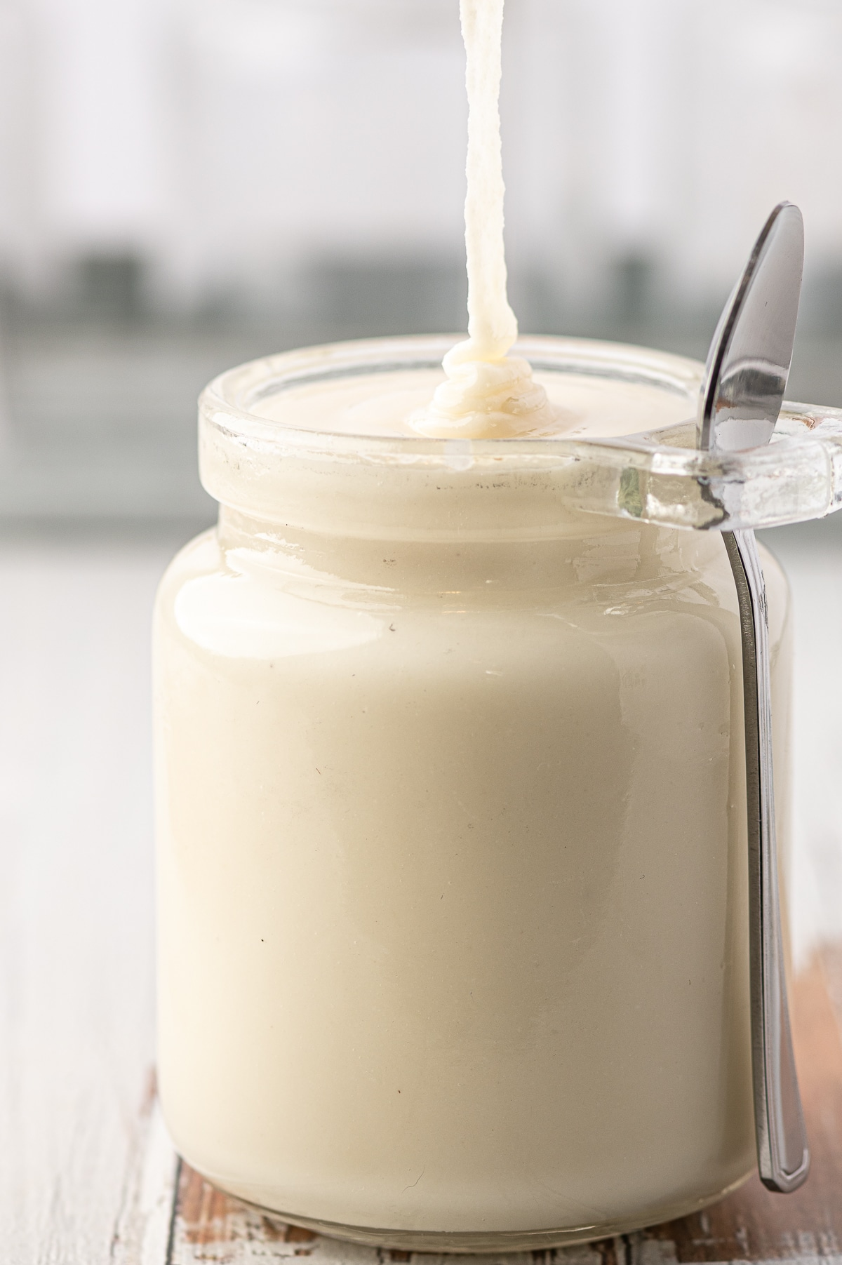 Just made low carb coconut butter being poured into a glass jar against a grey background