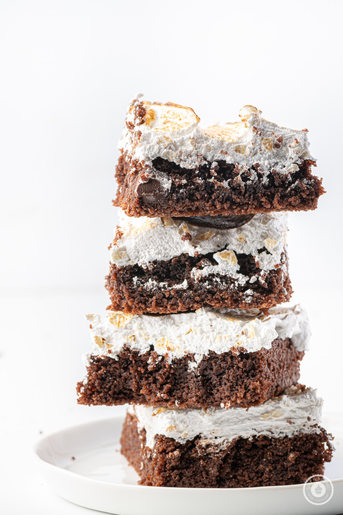 Low carb chocolate brownies with toasted marshmallow topping stacked  on a small white plate against a bright white background