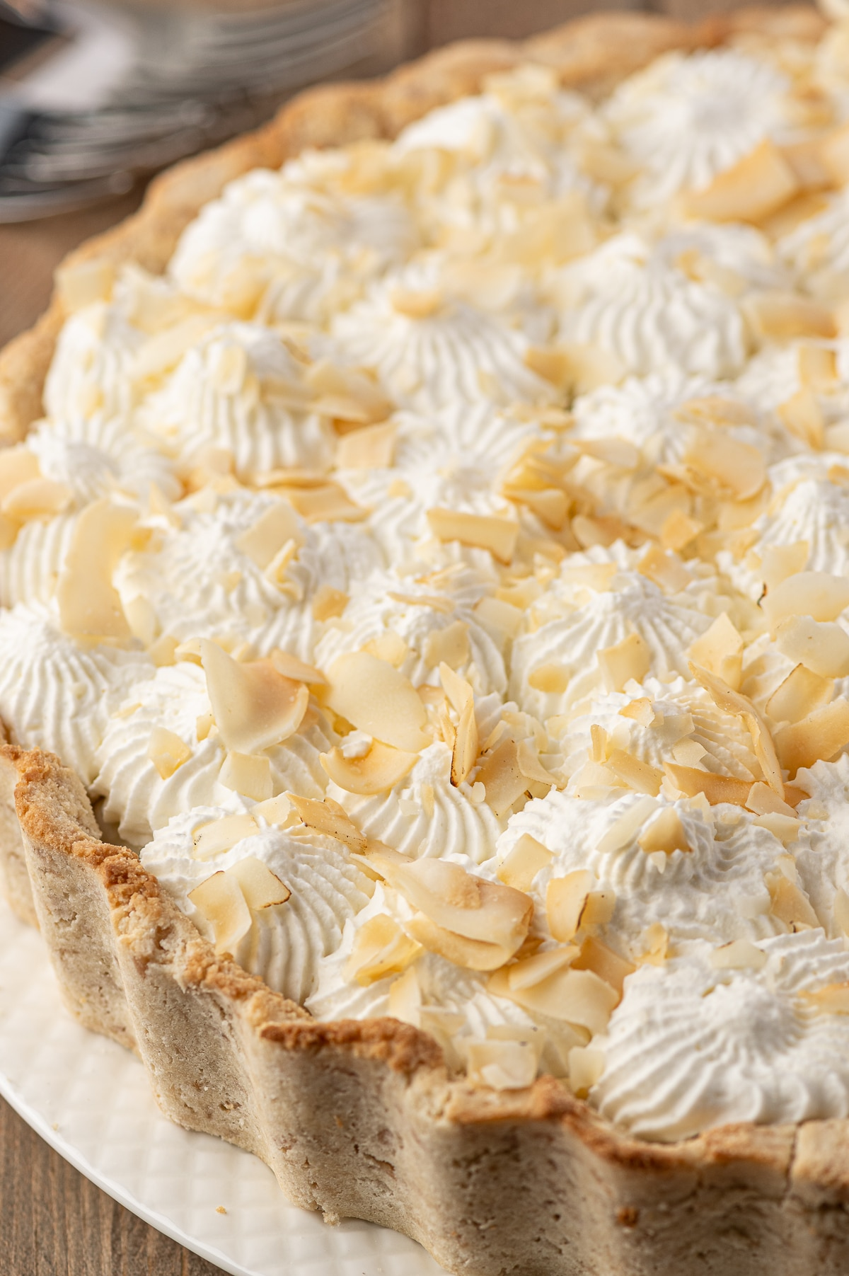 Coconut Cream Pie with ruffled crust, piped whipped cream stars and large flake toasted coconut.