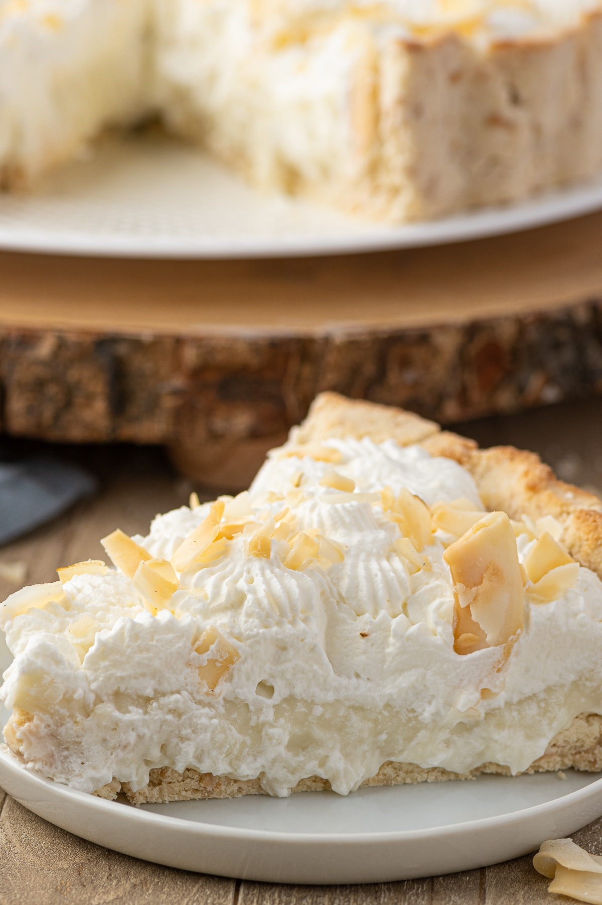 A close up photograph of a single slice of keto coconut cream pie with whipped cream topping and large toasted coconut flakes.