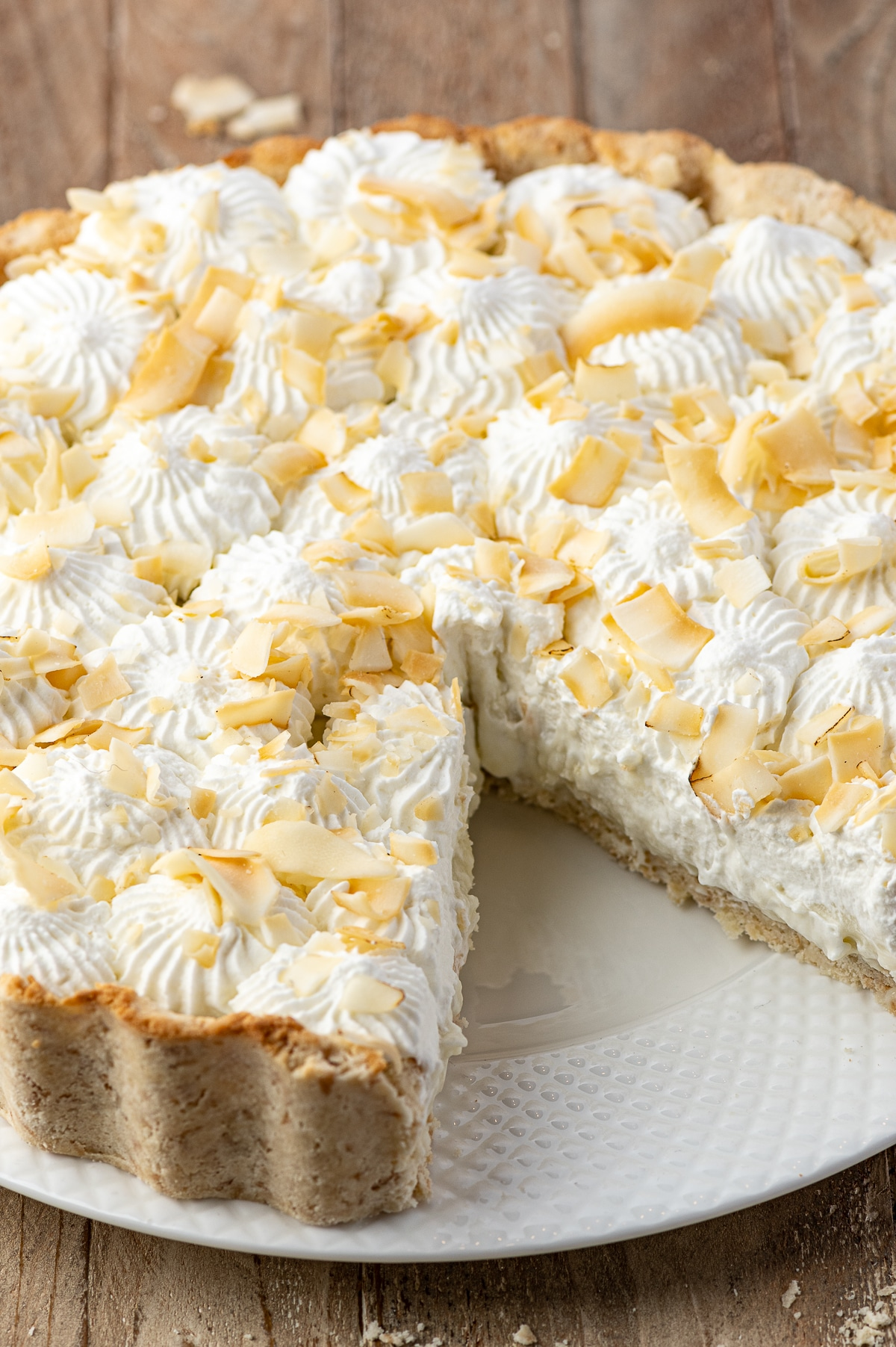 A close up shot of a coconut cream pie on a white texture plate with a slice removed.