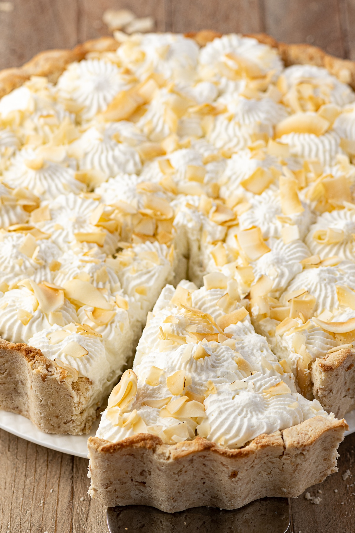 Coconut cream pie with a slice being removed on a rustic wooden table.