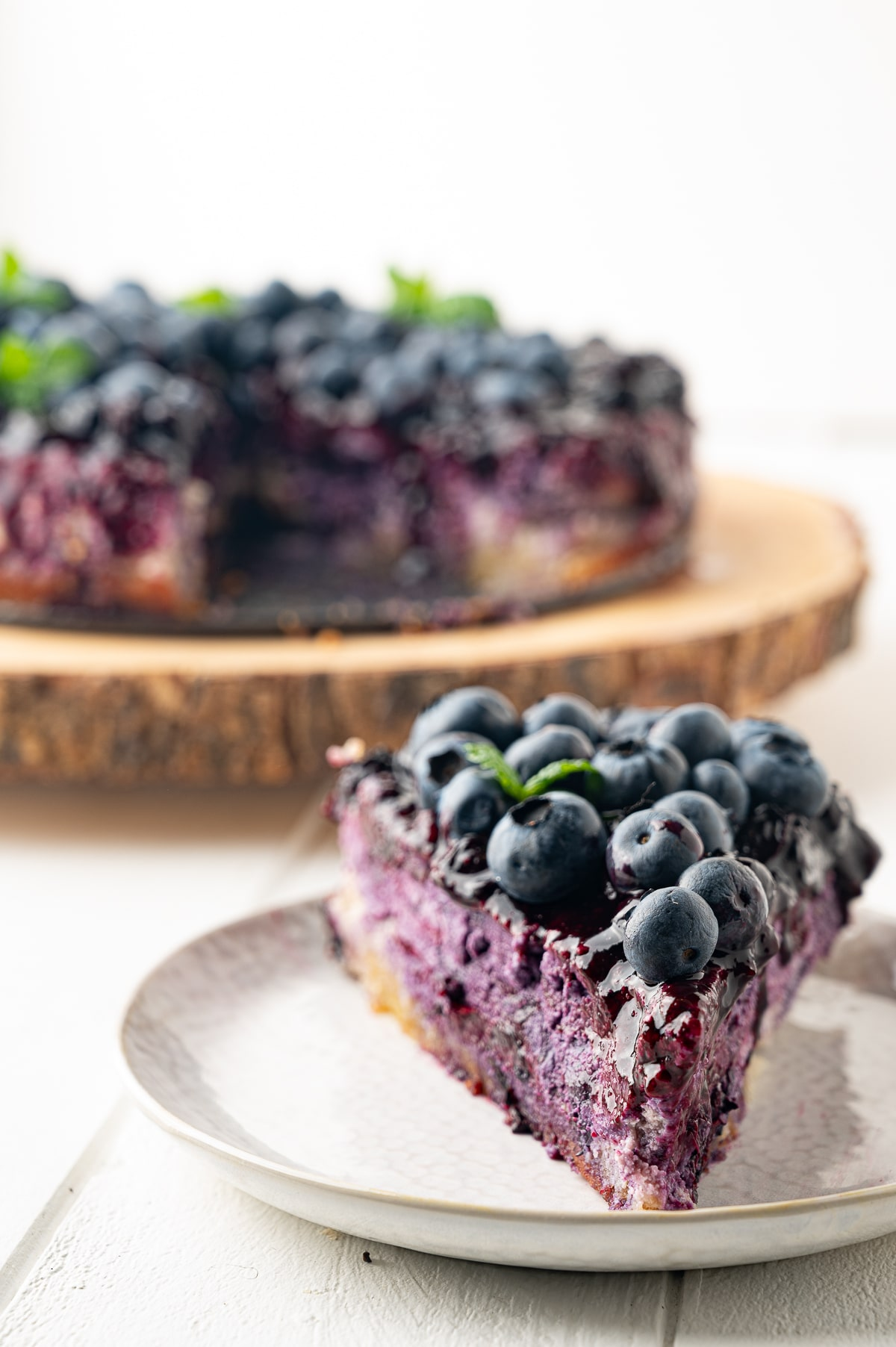 Bright violet colored slice of low carb blueberry cheesecake topped with fresh berries, blueberry drizzle and a sprig of fresh mint.  The cheesecake is in the background out of focus on a rustic wooden tray.