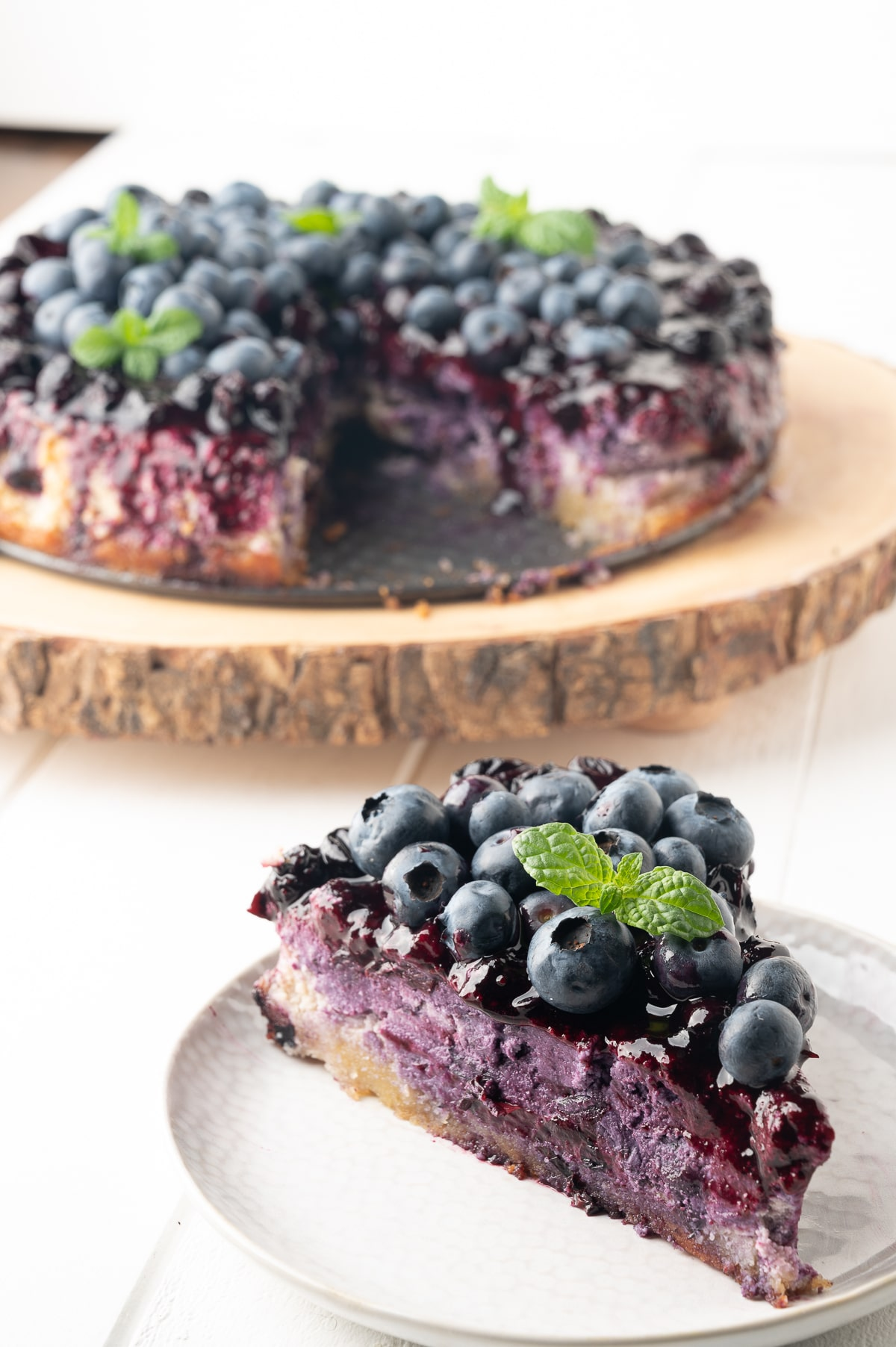 Bright violet colored blueberry cheesecake topped with fresh berries, blueberry drizzle and a sprig of fresh mint