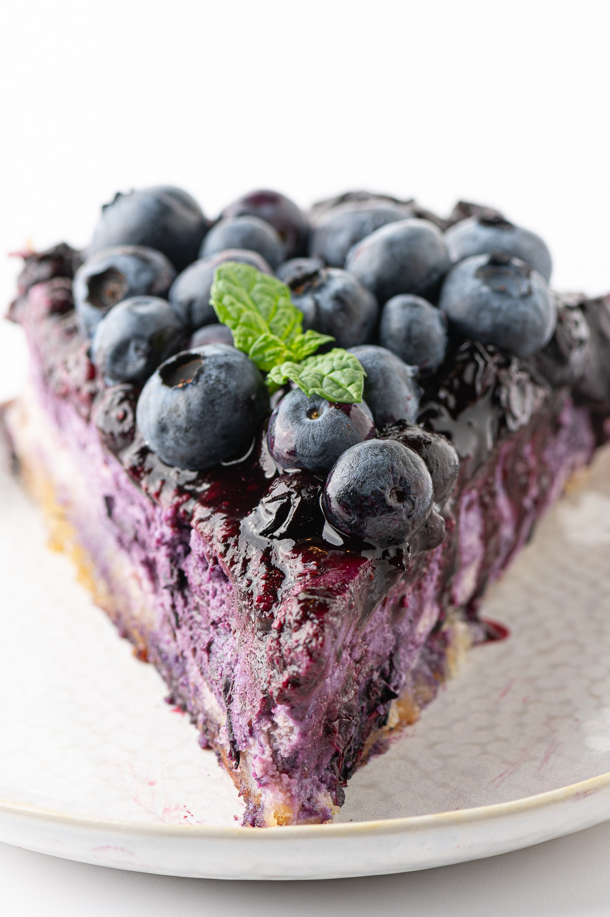 Bright violet colored low carb blueberry cheesecake topped with fresh berries, blueberry drizzle and a sprig of fresh mint