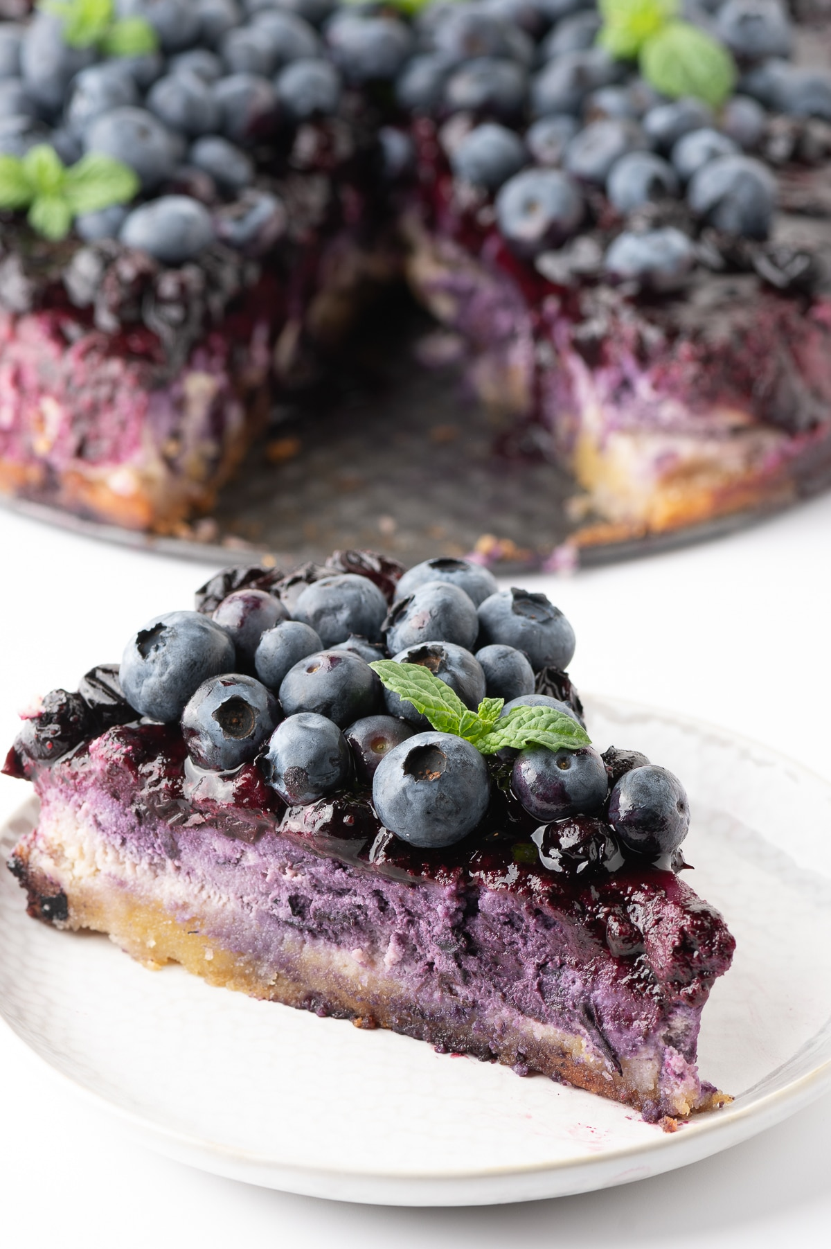 An up close photo of a piece of bright violet colored cheesecake topped with blueberry drizzle, fresh big bright blueberries and a sprig of bright green mint