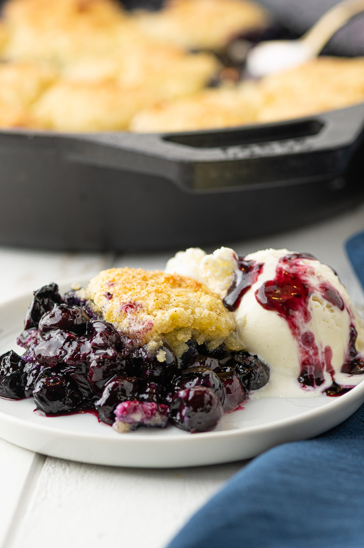 A plate of blueberry cobbler with a scoop of ice cream drizzled with blueberry syrup