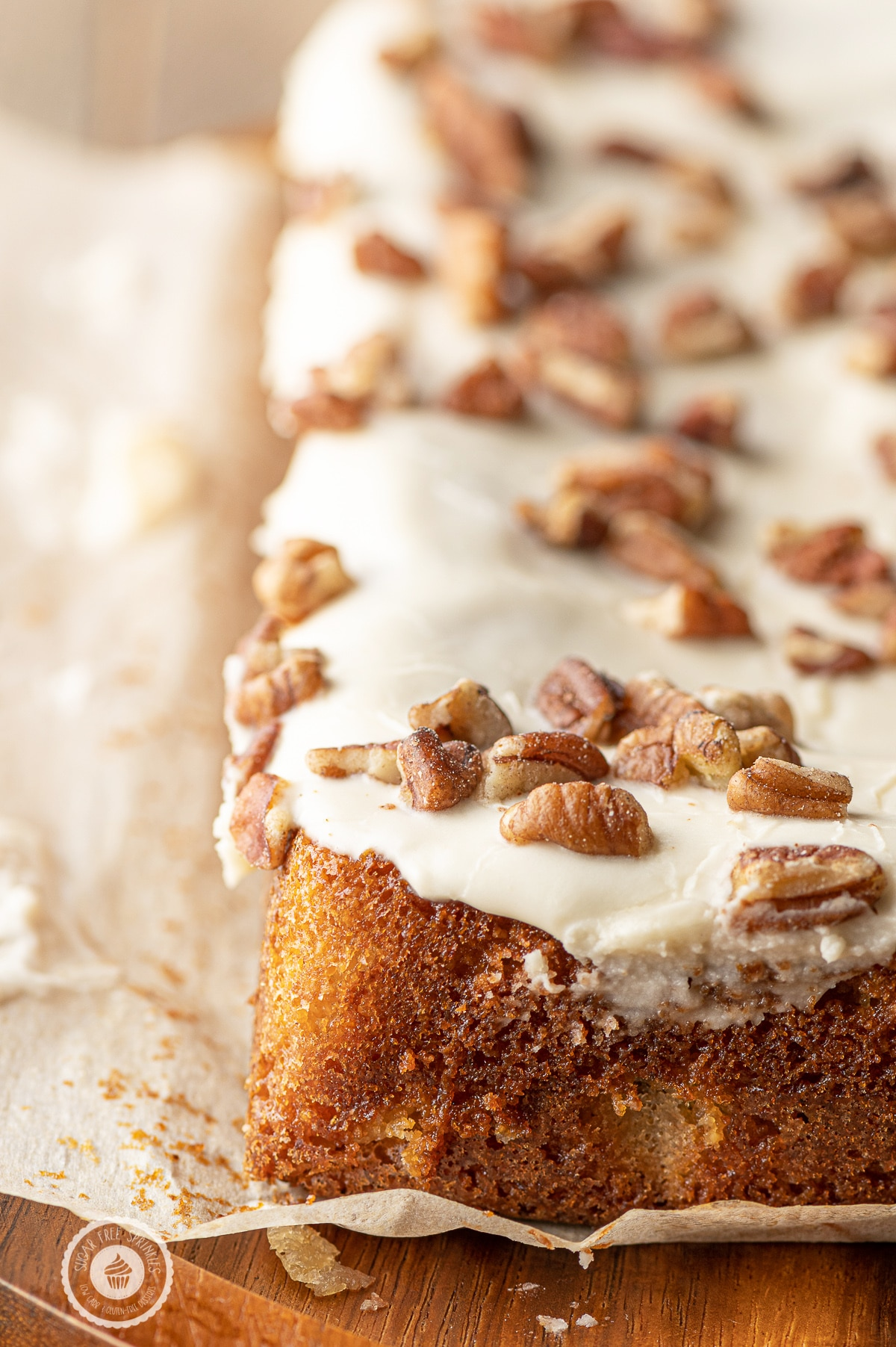 A slab of golden baked maple blondies with glaze and chopped pecans.
