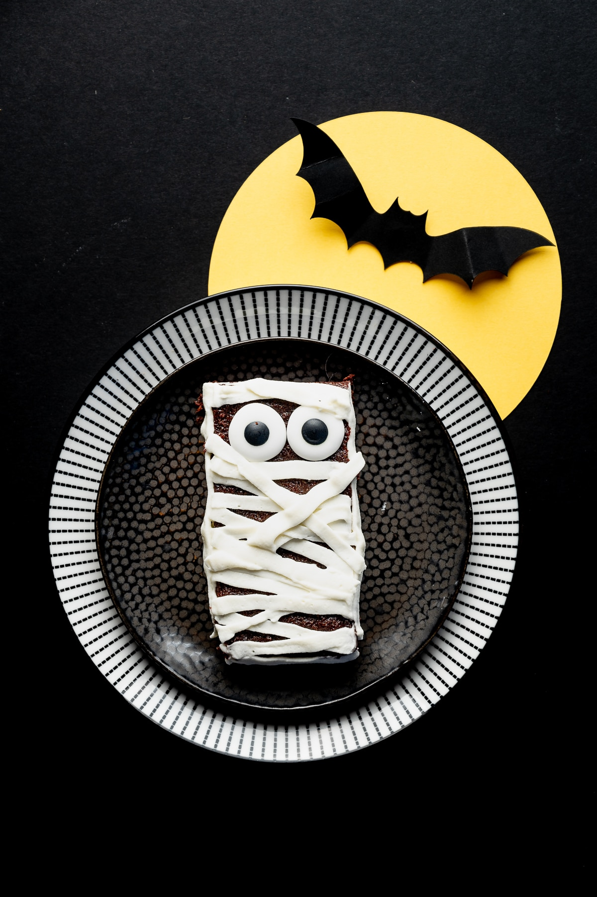 Sugar free brownie with googly eyes and frosting applied in strips to look like bandages on a black background with a bright yellow paper moon and paper bat