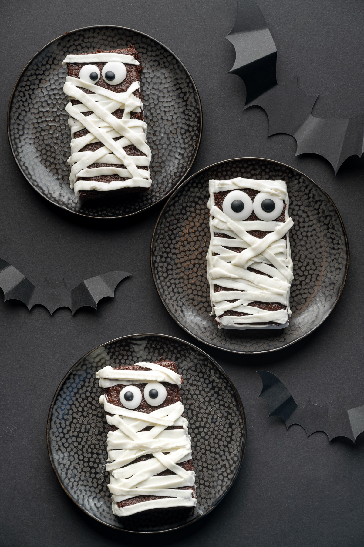Sugar free brownie with googly eyes and frosting applied in strips to look like bandages on a black background