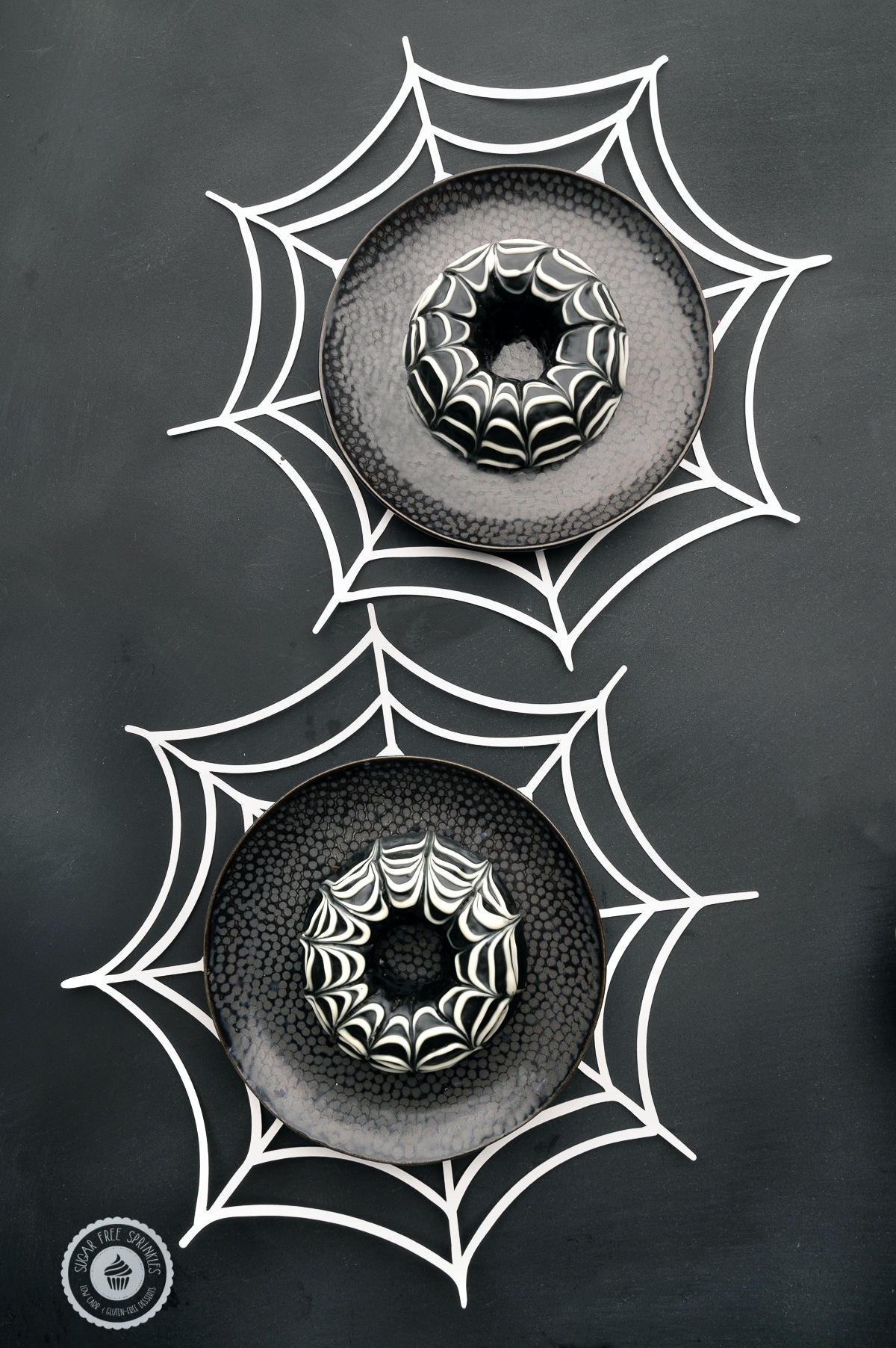 Chocolate glazed keto donuts with a spider web design on dark black plates with white paper spider webs