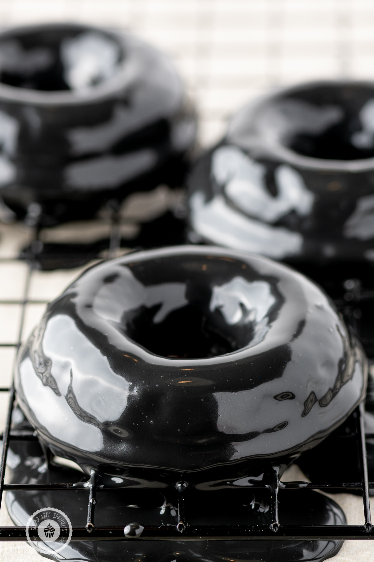 Black shiny ganache coated donuts on a cooling rack