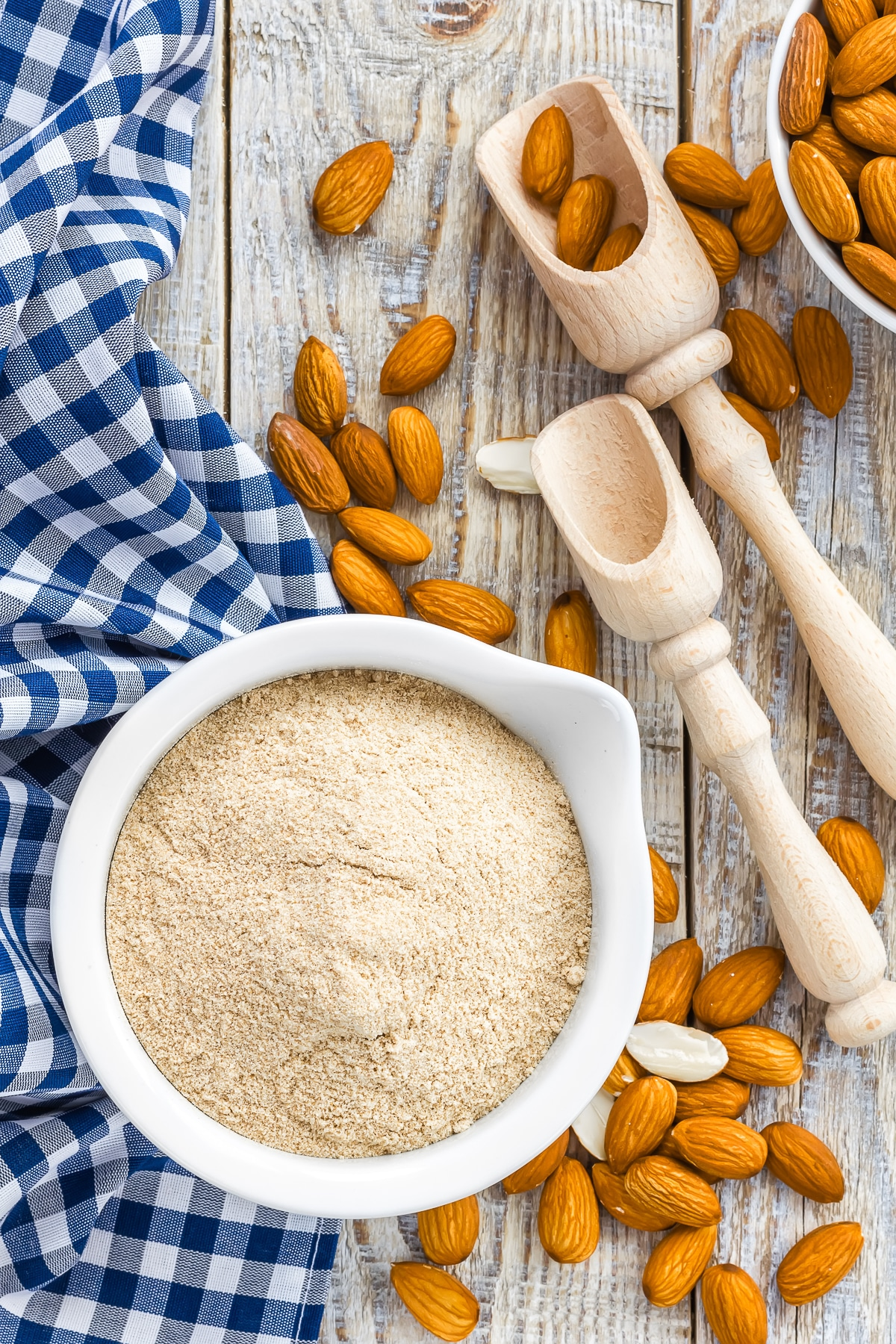 A small bowl of fine ground almond flour on top of a blue gingham napkins surrounded by wooden scoops and whole raw almonds